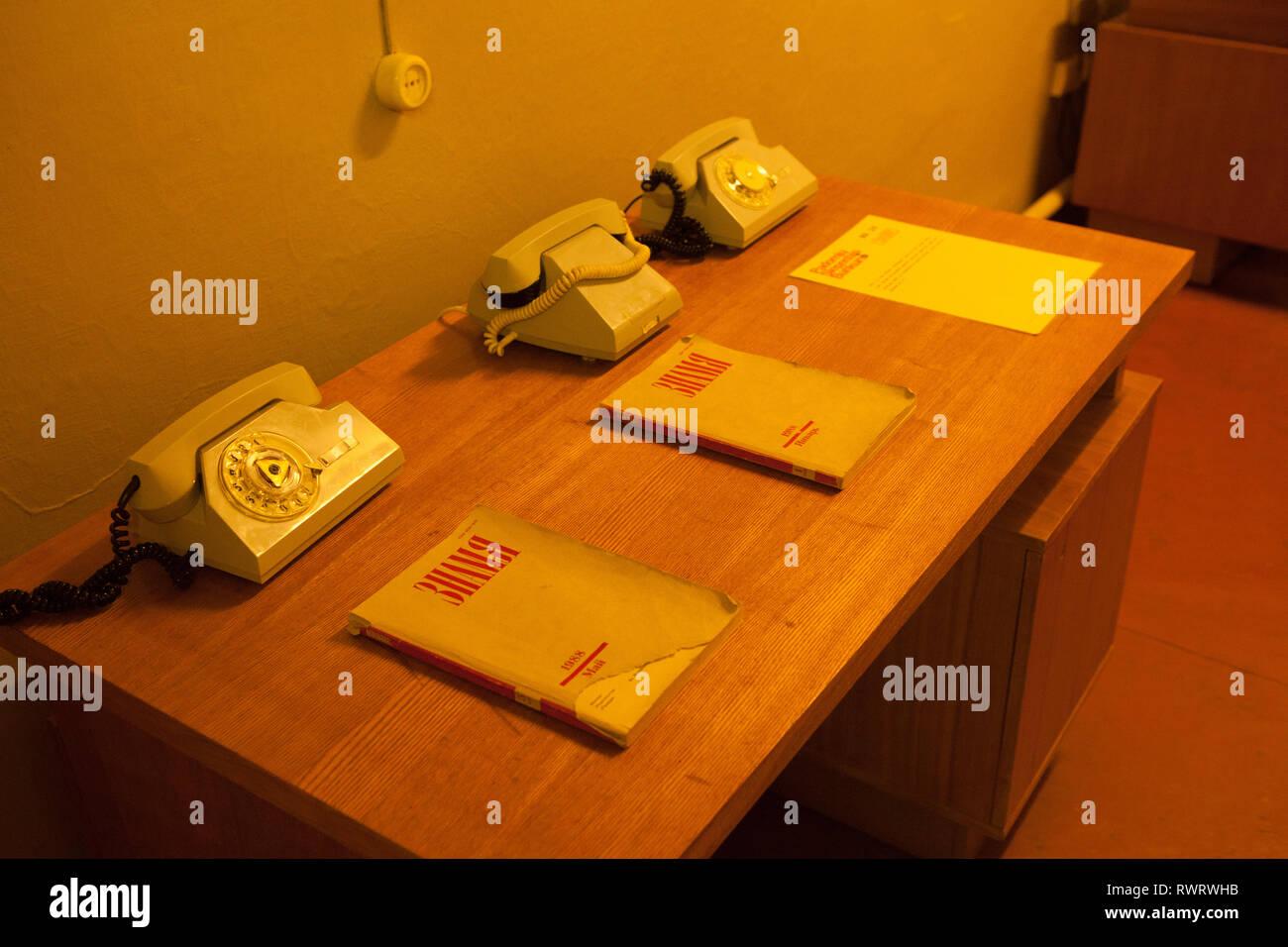 Fila de teléfonos alámbricos y manuales sobre el escritorio en el búnker de la guerra fría, Ligatne, Letonia Imagen De Stock
