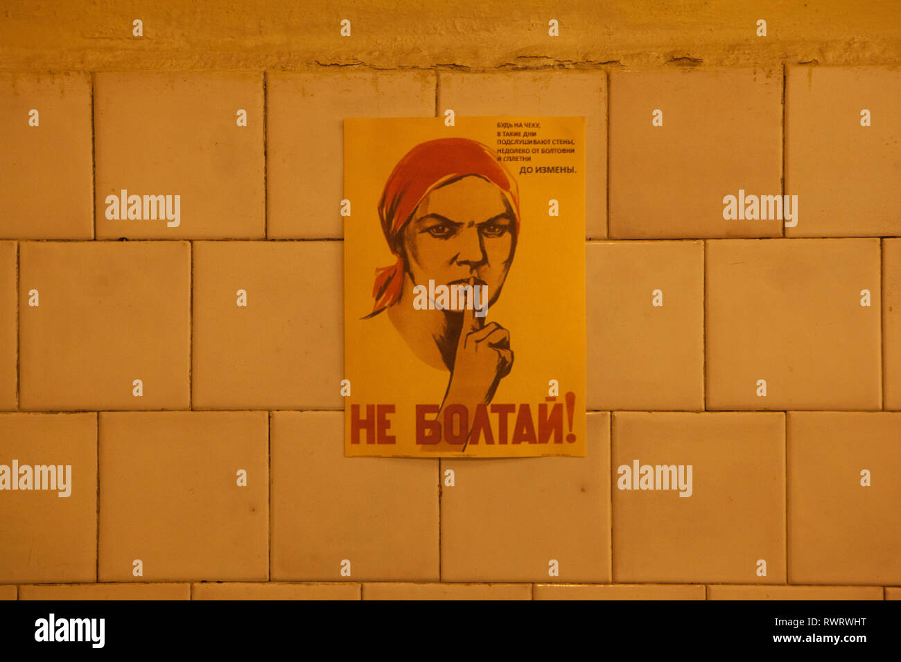 Carteles de propaganda política de la mujer con el dedo en los labios en la guerra fría, el búnker Ligatne, Letonia Imagen De Stock
