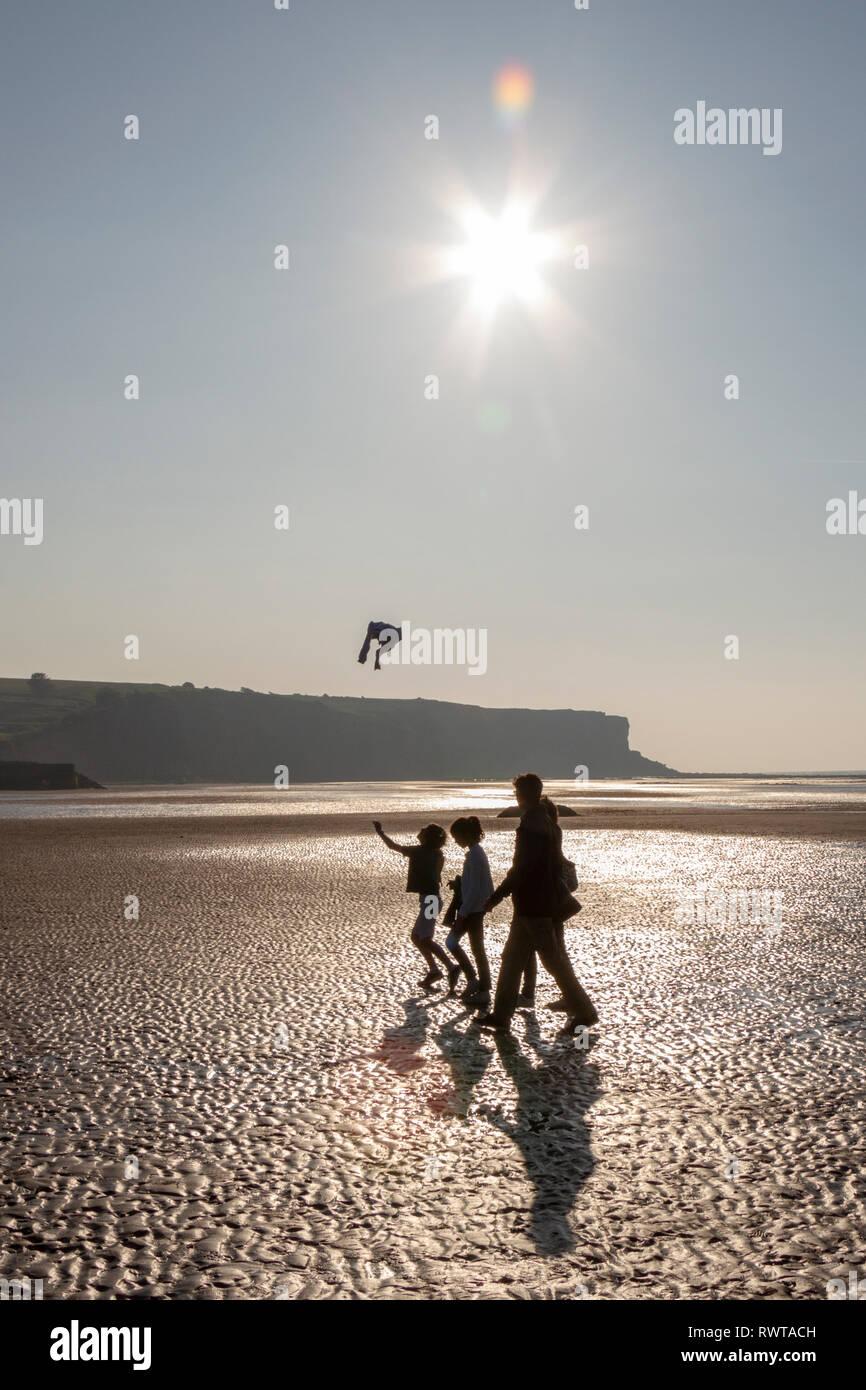 Una familia caminando por la playa con marea baja en una brillante noche en Arromanches-les-Bains en sunset beach, Normandía, Francia. Foto de stock