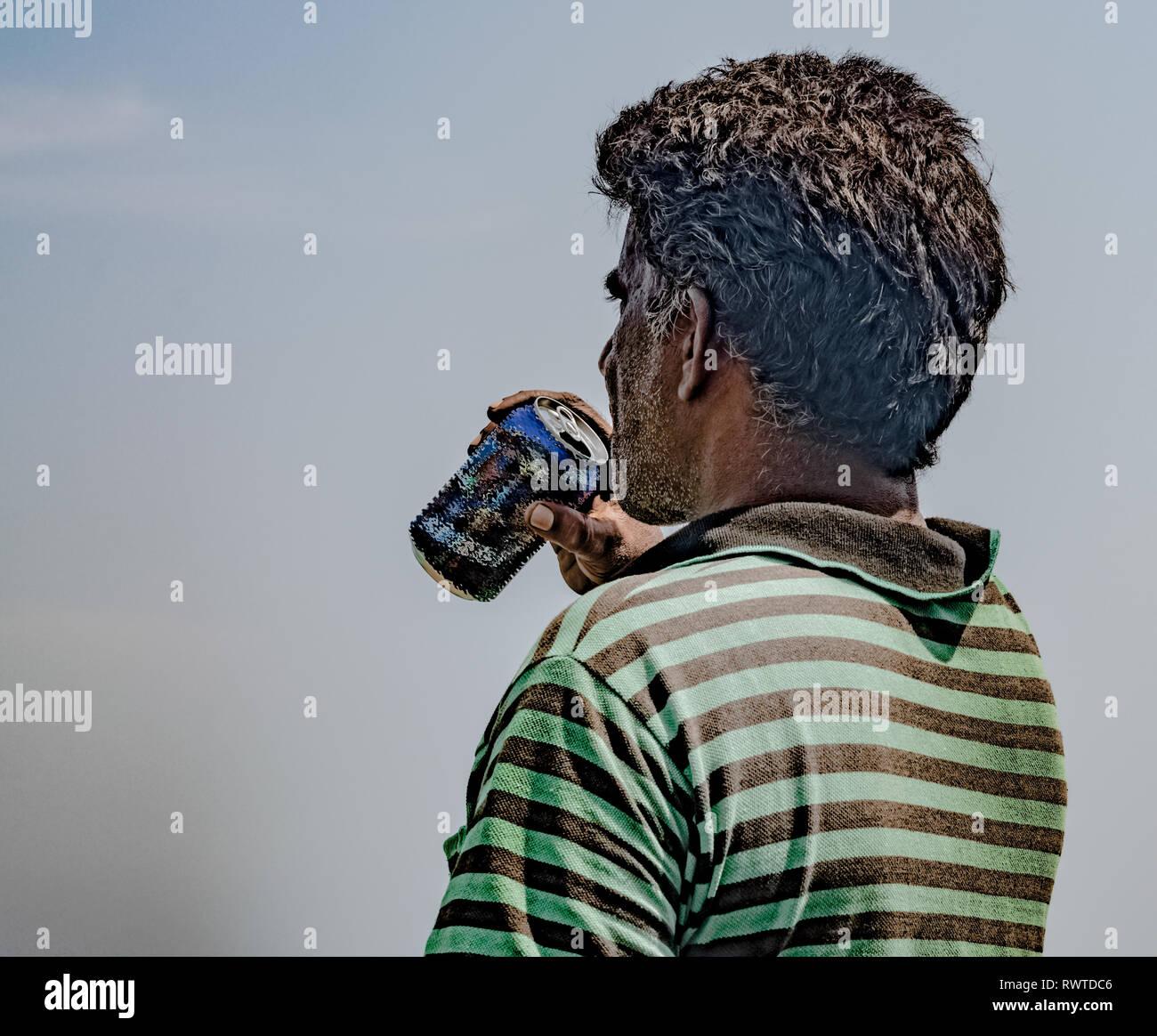 Pescador de mediana edad de origen surasiático, vistiendo striped tshirt está agotada y saciar su sed por beber cerveza o bebida fría en los calurosos días soleados Imagen De Stock