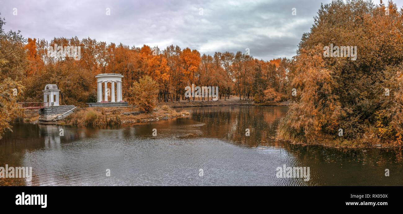 Estanque en un parque verde de la ciudad con una rotonda a finales del otoño dorado Foto de stock