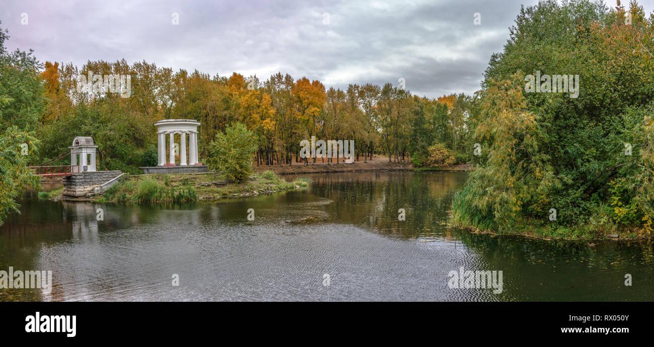 Estanque en un parque verde de la ciudad con una rotonda a principios de otoño Foto de stock
