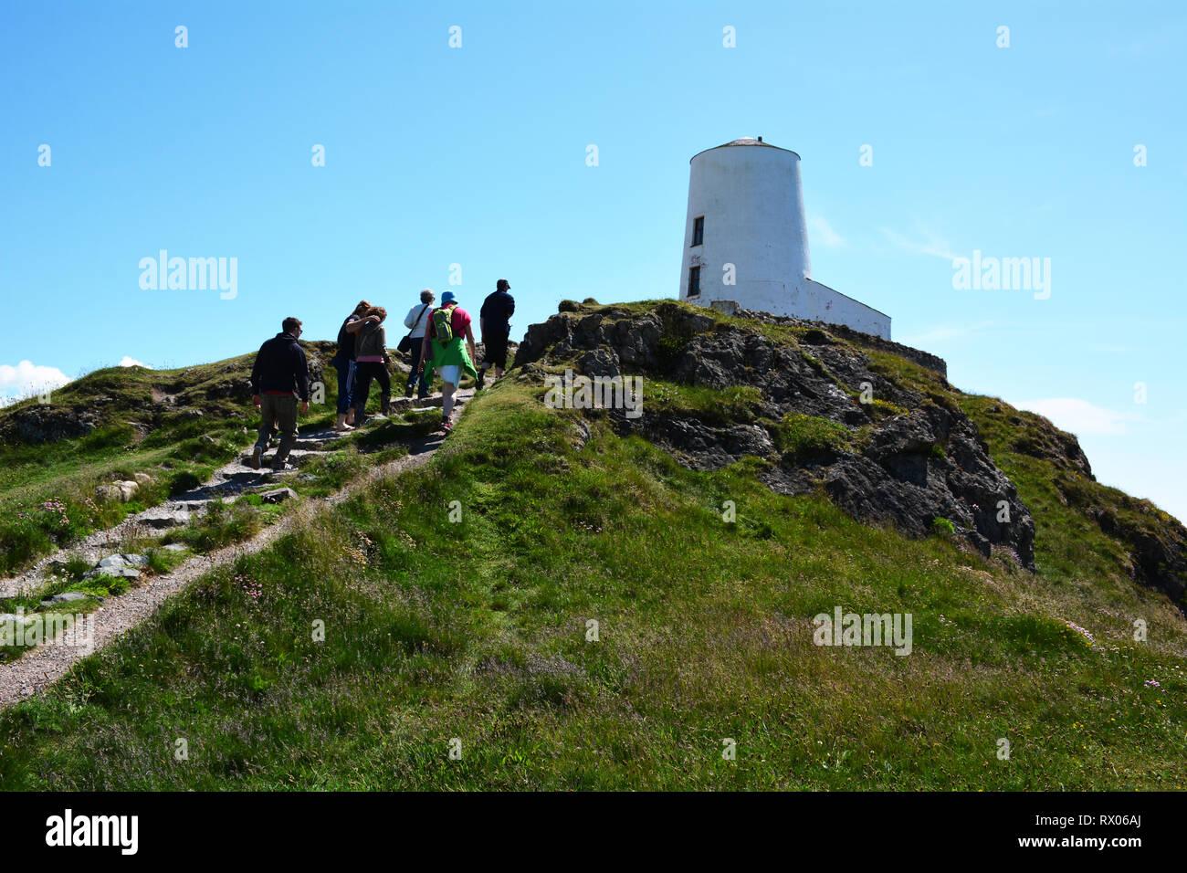 Caminando hasta Twr Mawr Llanddwyn faro en la Isla de la costa de Anglesey Foto de stock