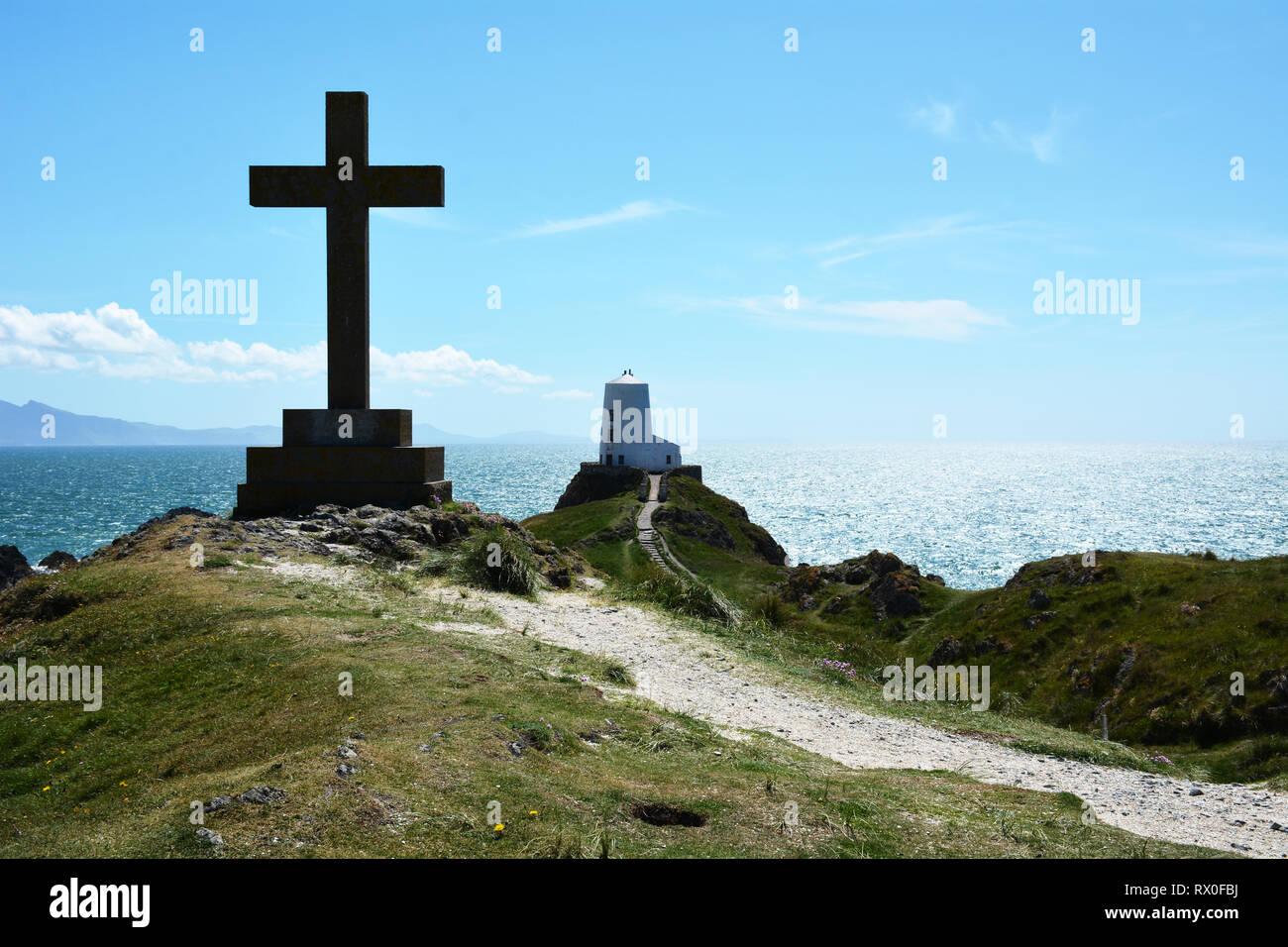 La cruz y Twr Mawr faro en Llanddwyn isla frente a la costa sur oeste de Anglesey en el norte de Gales. Foto de stock