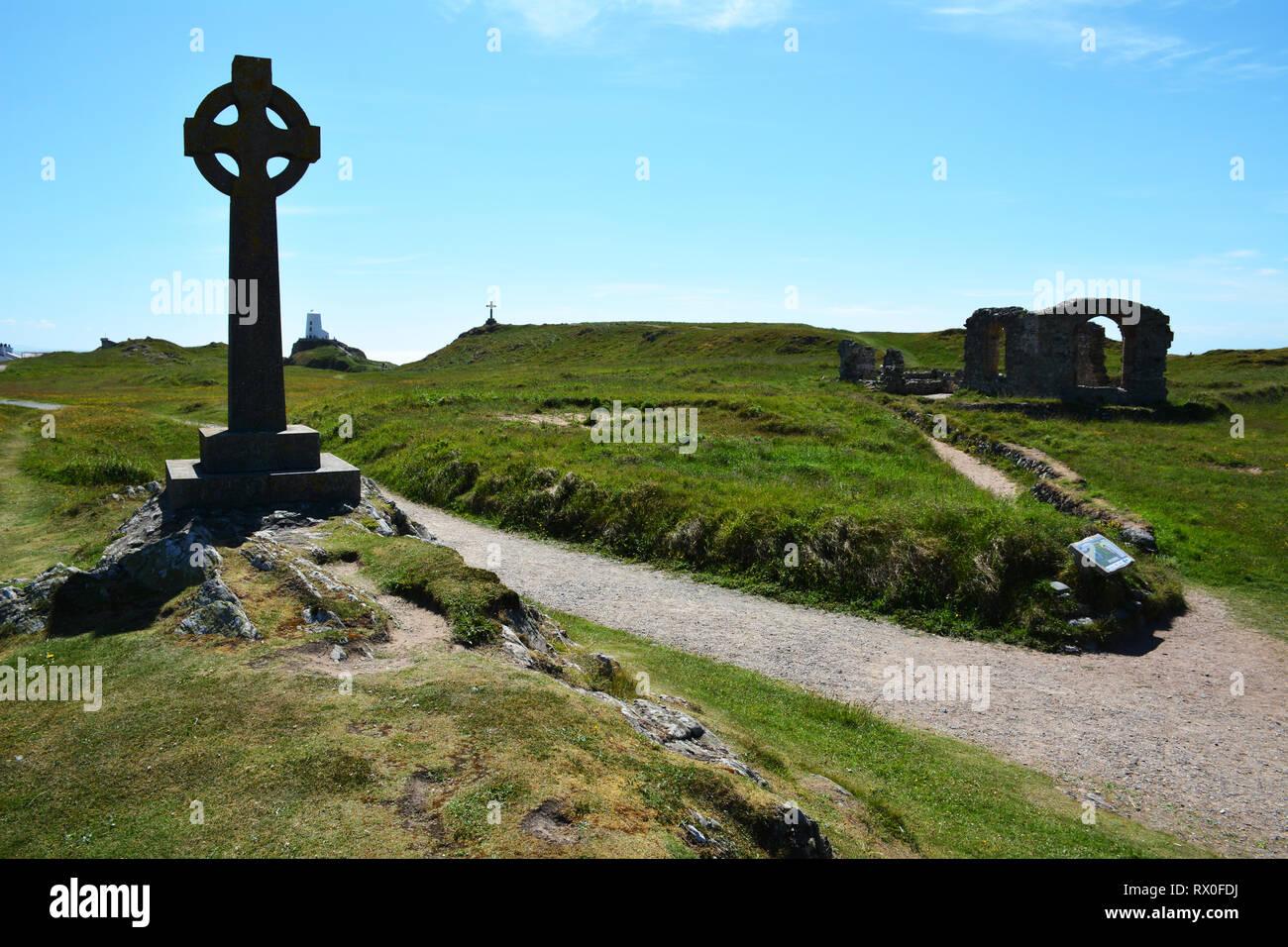 Las cruces, la iglesia y el faro en la isla Llanddwyn frente a la costa de Anglesey Foto de stock