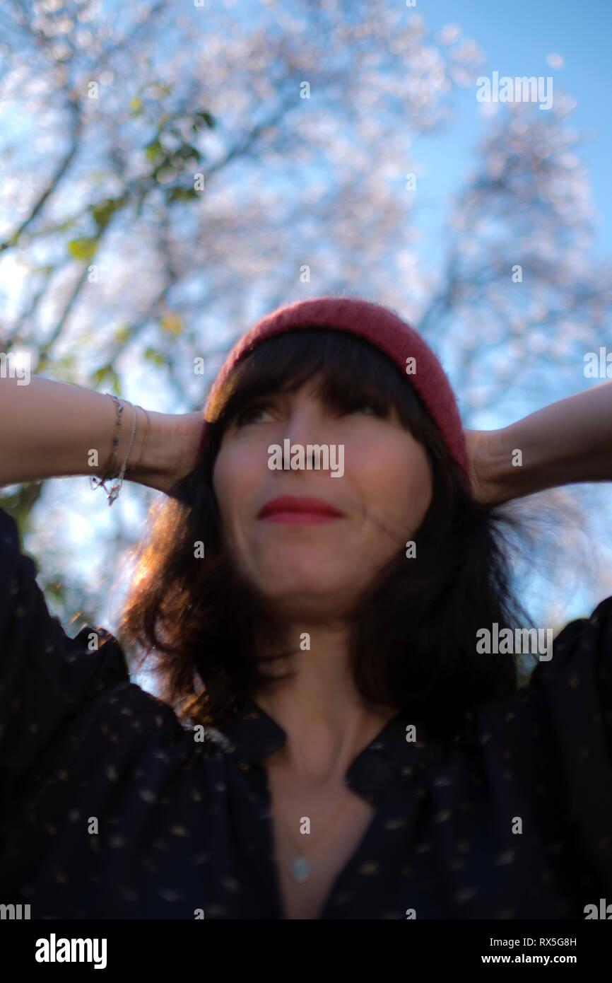 Ángulo bajo de cerca de la hermosa mujer francesa con sombrero de lana y sus manos detrás de su cabeza, mirando relajado y feliz sobre el advenimiento de la primavera Foto de stock