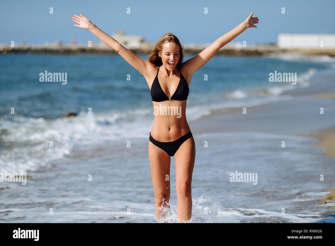 5b81f47ce Joven Mujer rubia con hermoso cuerpo en traje de baño en una playa tropical  con los