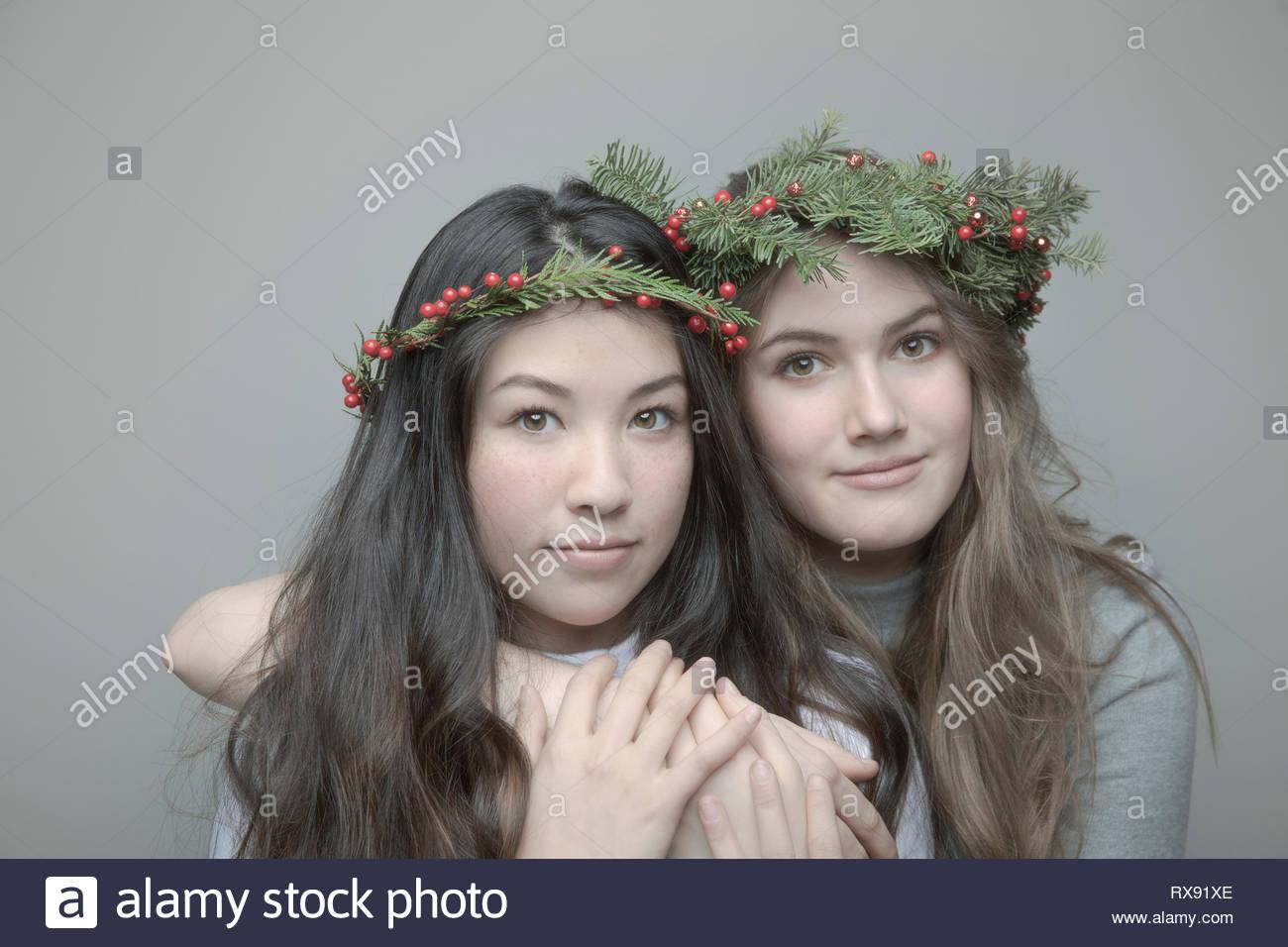 Retrato seguros hermoso adolescente amigos vestidos de navidad coronas en la cabeza. Imagen De Stock