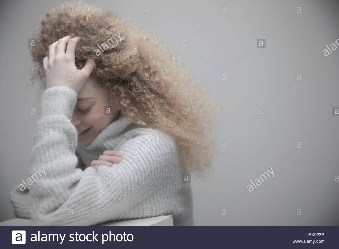 Retrato joven y bella mujer rubia con el pelo rizado y largo la cabeza entre las manos Imagen De Stock