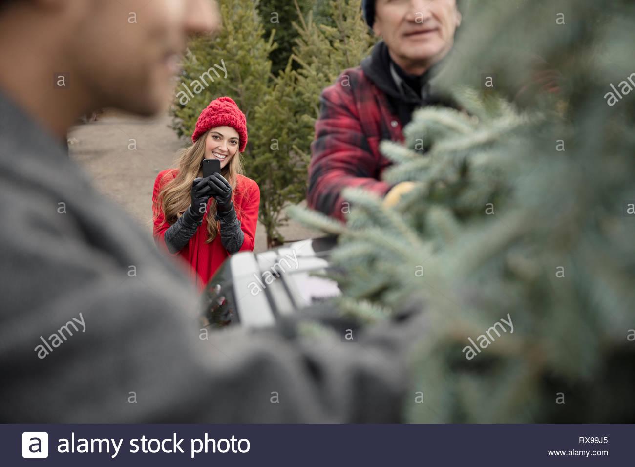 Mujer con teléfono con cámara de fotografiar novio compras de árbol de Navidad en el mercadillo de navidad Imagen De Stock