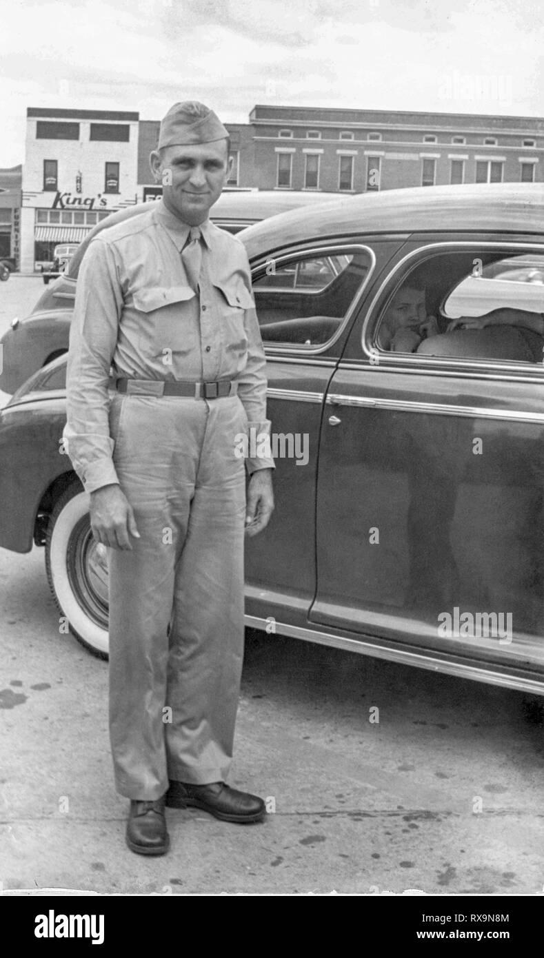 Disparo vertical del joven soldado americano en uniforme de pie junto a un coche justo antes de que la Unión de la implementación. Antigua digitalizada foto de familia. Puede contie Imagen De Stock