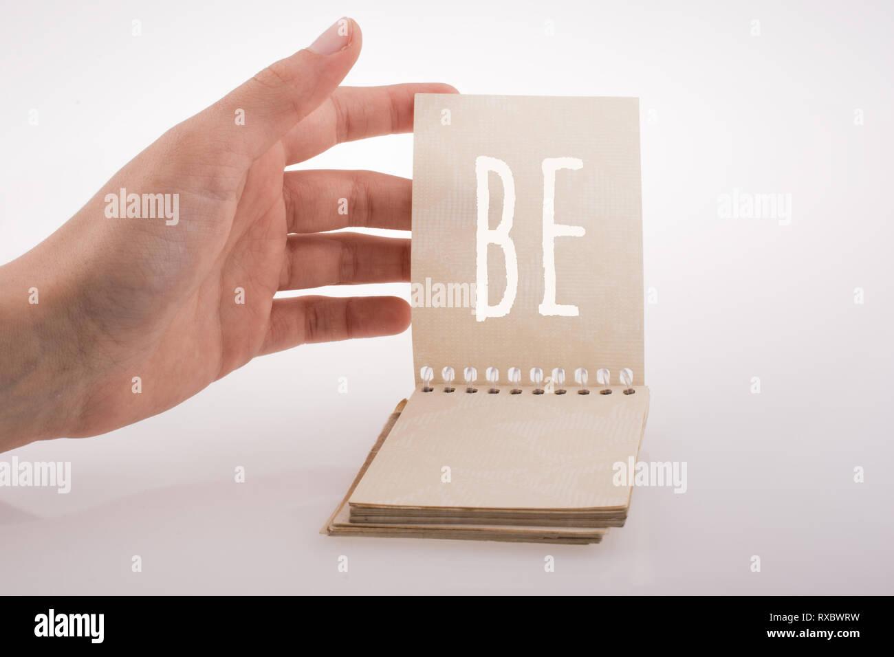 Explotación de mano portátil con ser palabra sobre un fondo blanco. Imagen De Stock