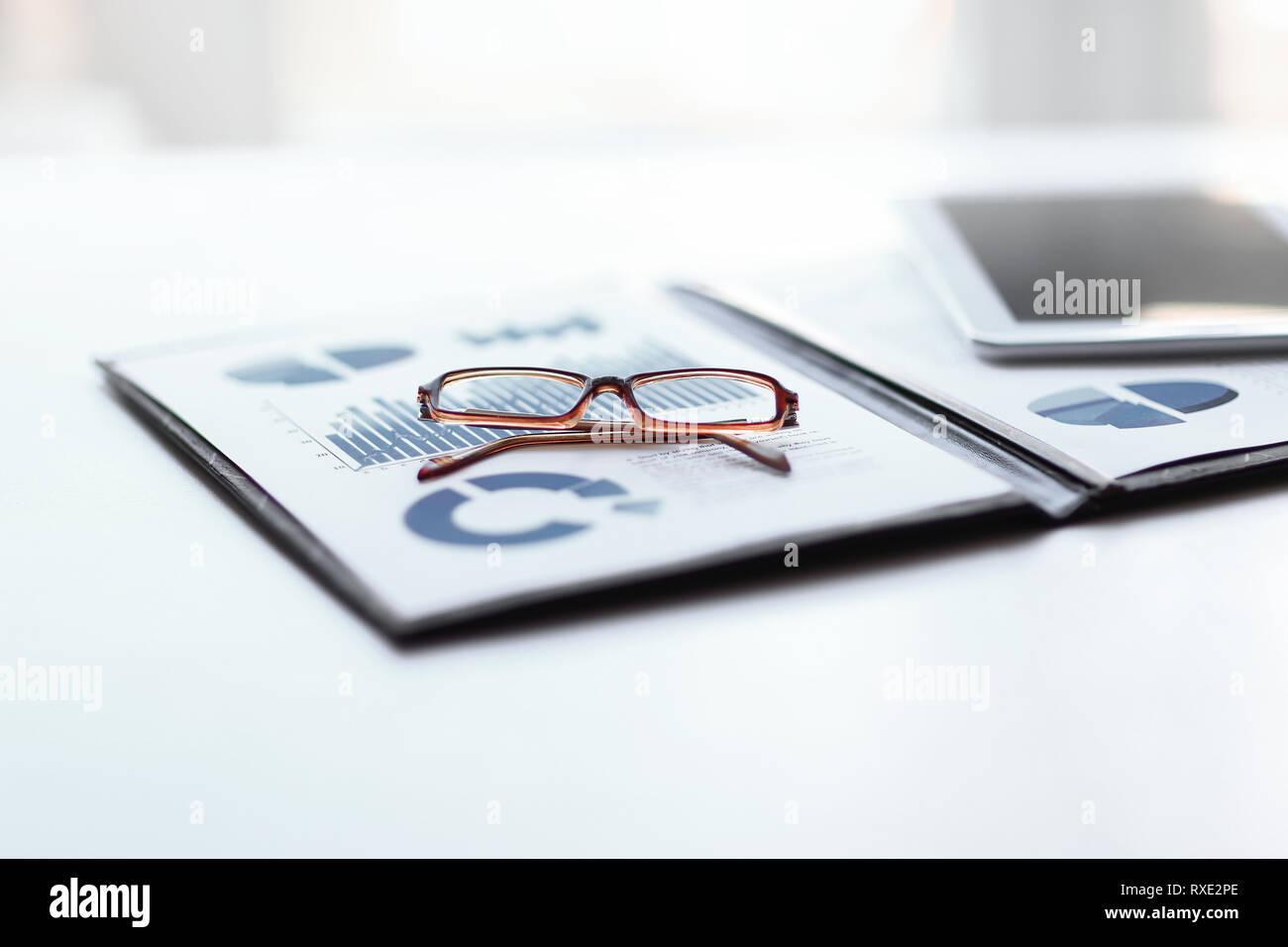 Portapapeles con el informe financiero y los vasos en el escritorio Foto de stock