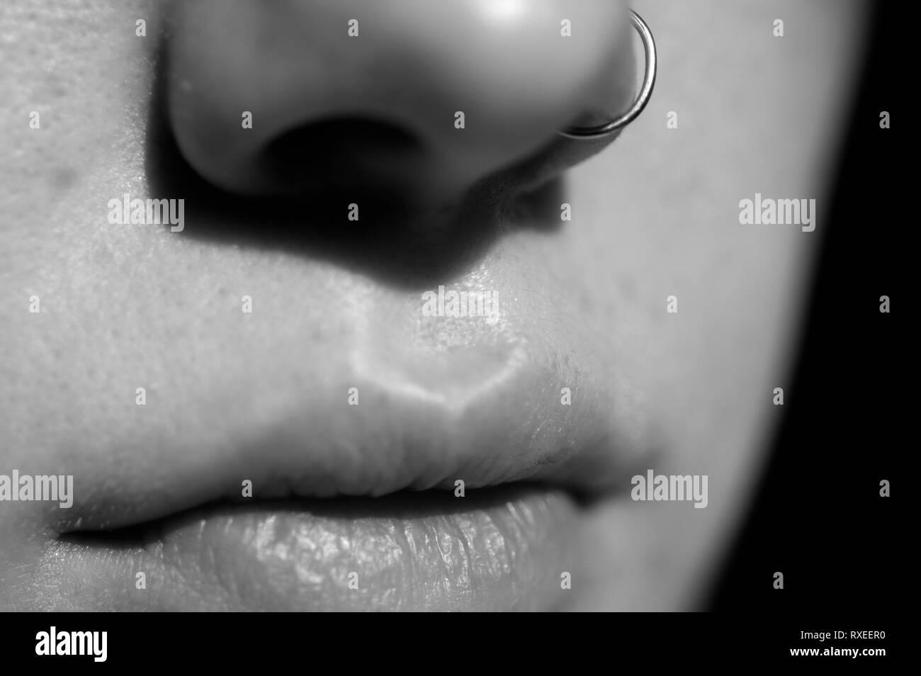 Una imagen en blanco y negro de una joven mujer en la boca y la nariz con un anillo de la nariz y el negro como color de fondo. Foto de stock