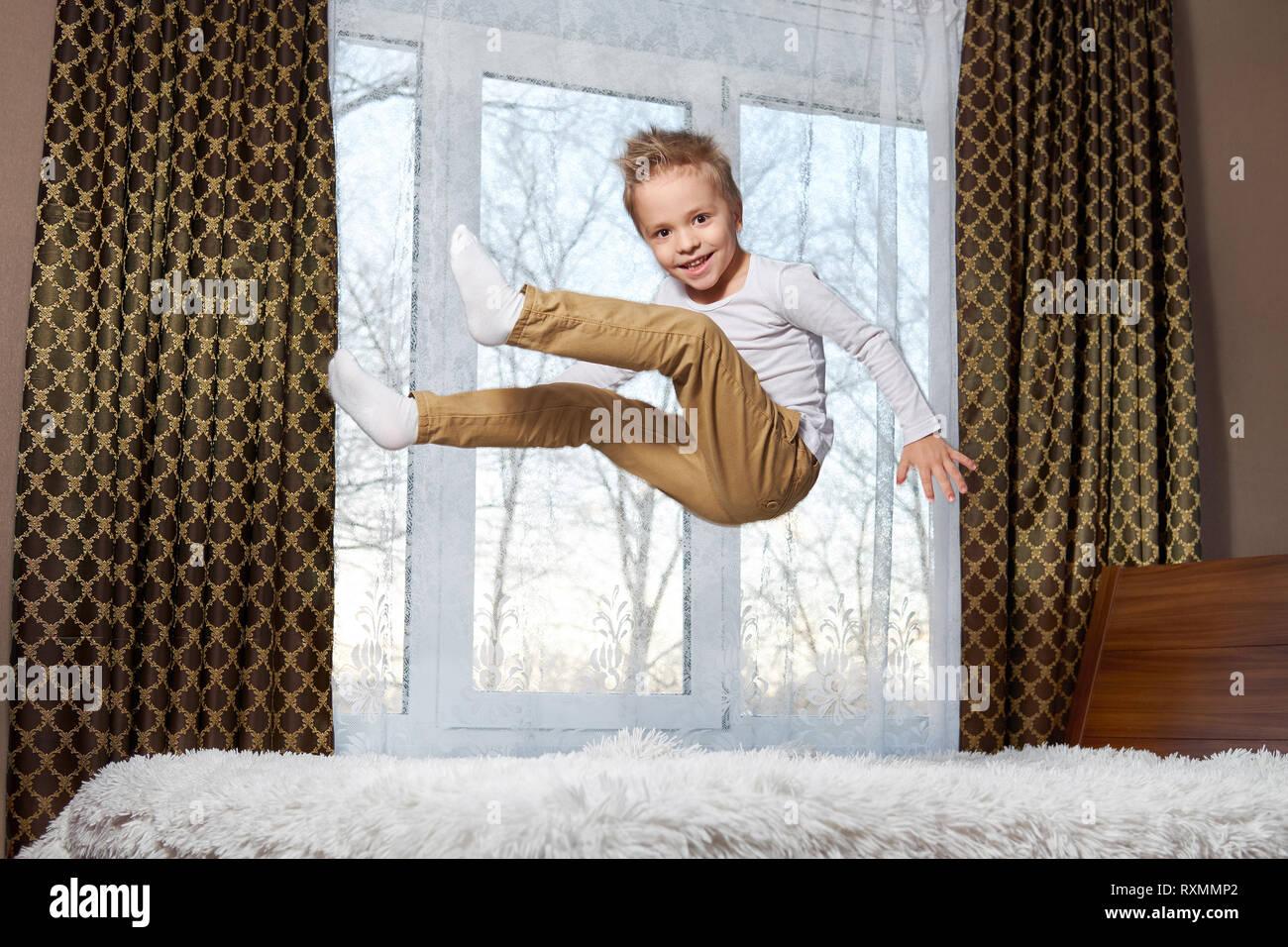 Niño fun home. Hermosa rubia niño de 6 años de edad jugando mañana a la habitación. Kid sonriente al dormitorio, saltando sobre la cama. Foto de stock