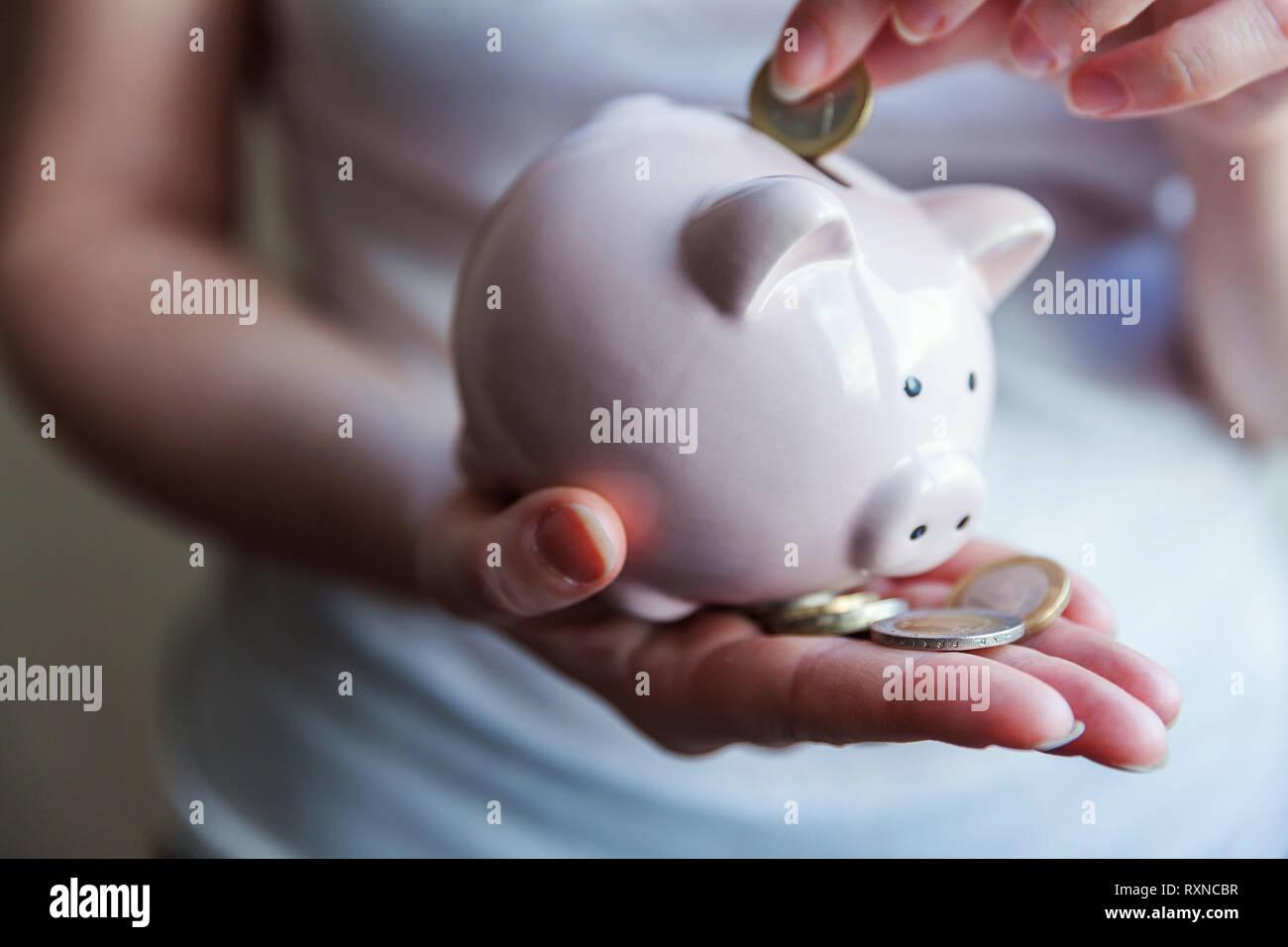 Mujer femenina manos sosteniendo rosa hucha y poner dinero monedas de euro. Presupuesto de Inversión Ahorro Jubilación riqueza empresarial financiera concepto bancario de dinero Foto de stock
