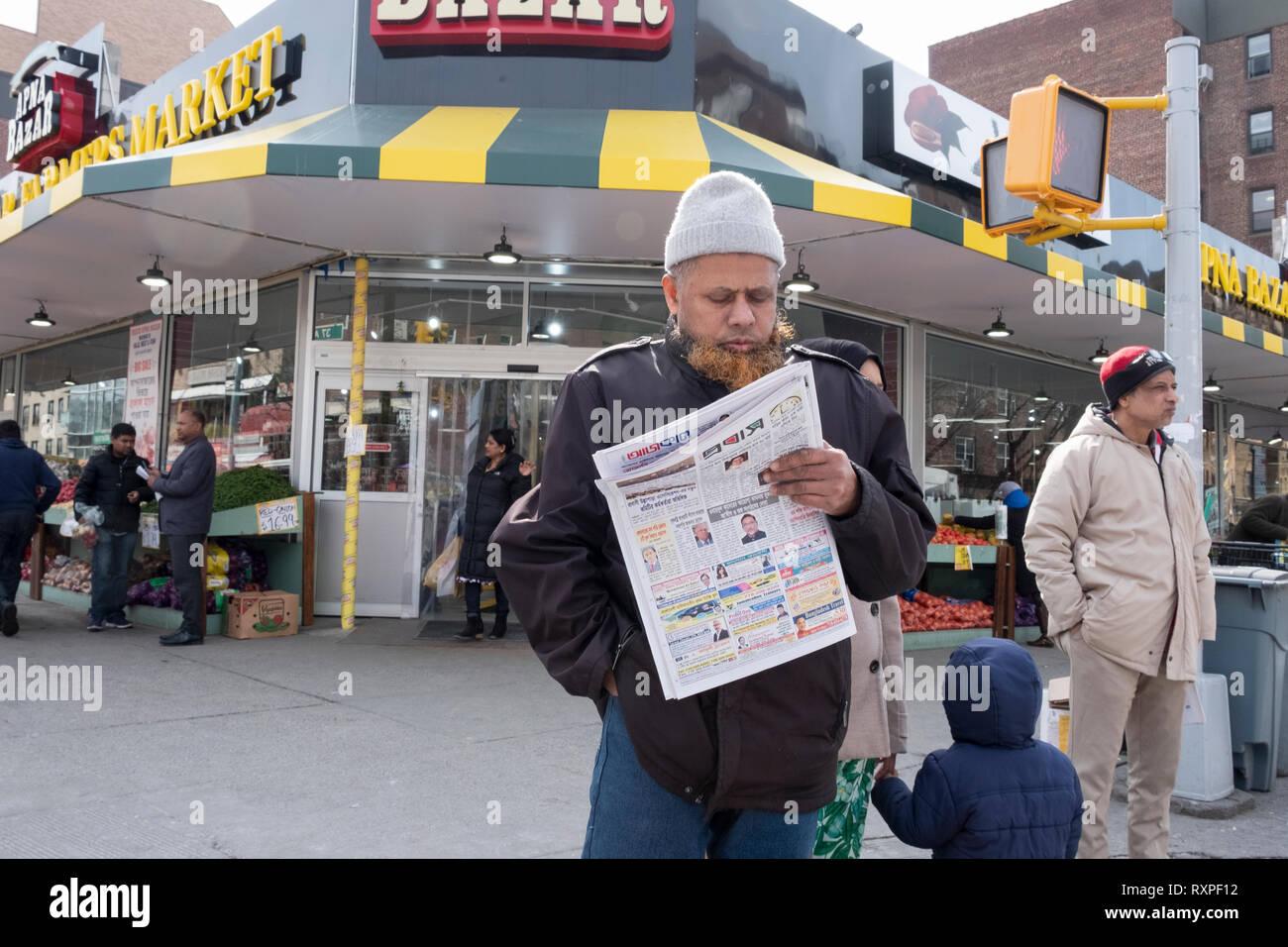 Un hombre musulmán con una barba teñida con henna lee un periódico bengalí en 37th Avenue en Jackson Heights, Queens, Ciudad de Nueva York. Imagen De Stock