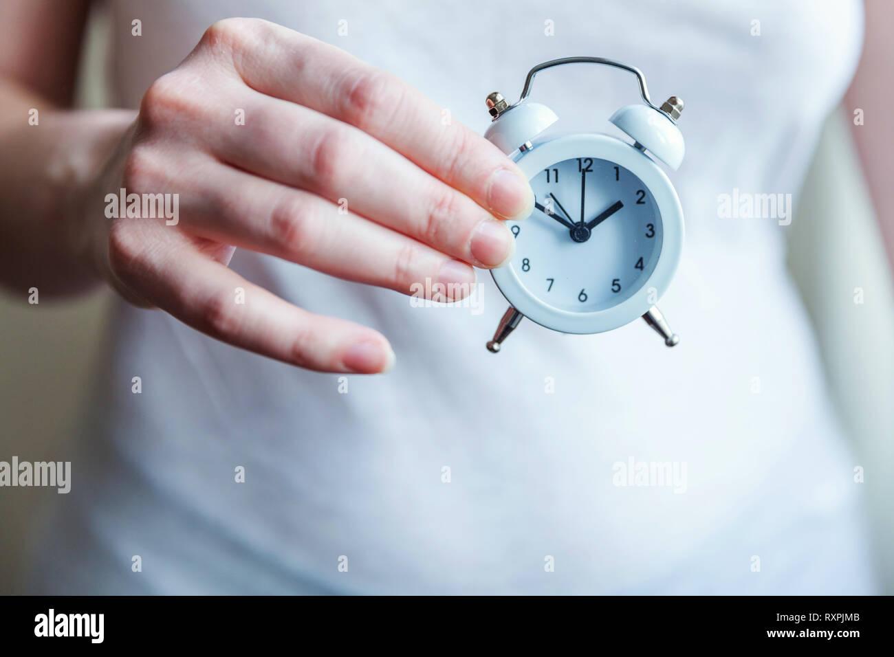 Mujer femenina manos sosteniendo sonando twin bell vintage clásico de despertador. El tiempo de descanso de la vida buenos días, noche despertarse despierto concepto Foto de stock
