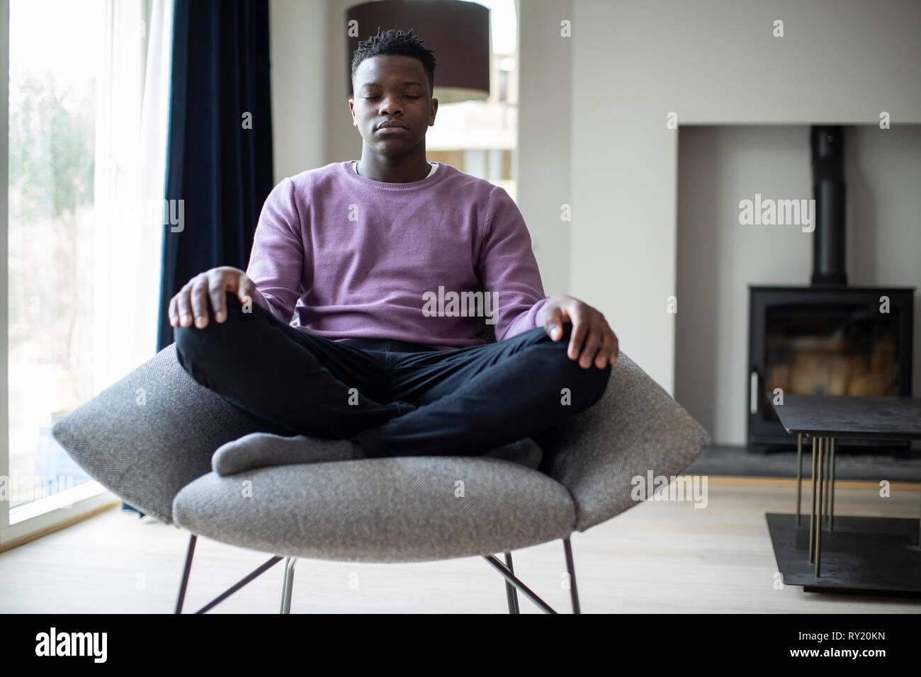 Cerca de pacíficos Adolescente meditando sentado en una silla en casa Imagen De Stock