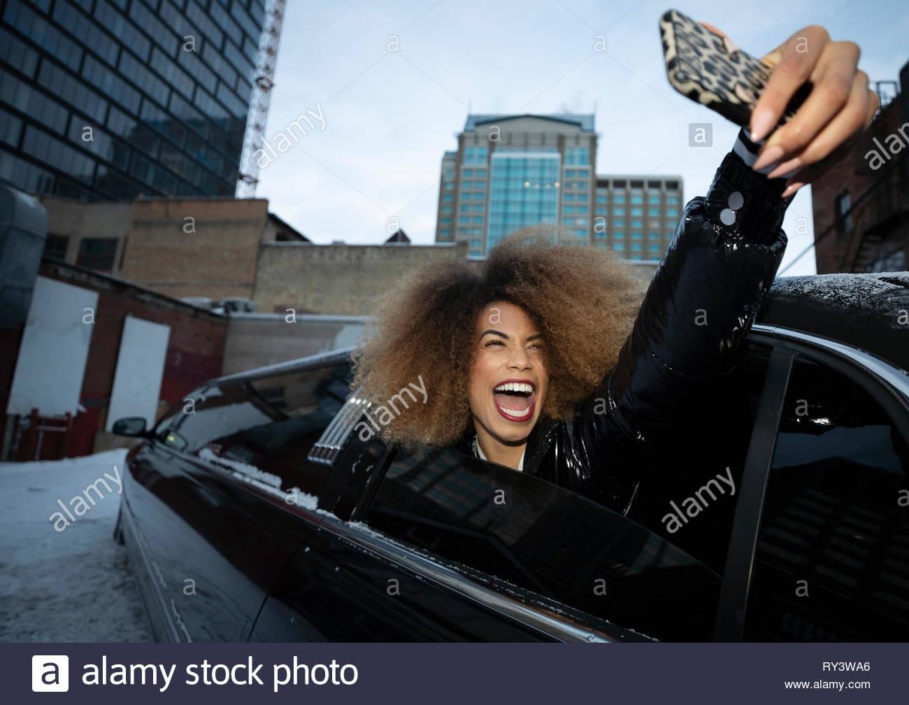Exuberante mujer joven tomando selfie en ventana de limusina Imagen De Stock
