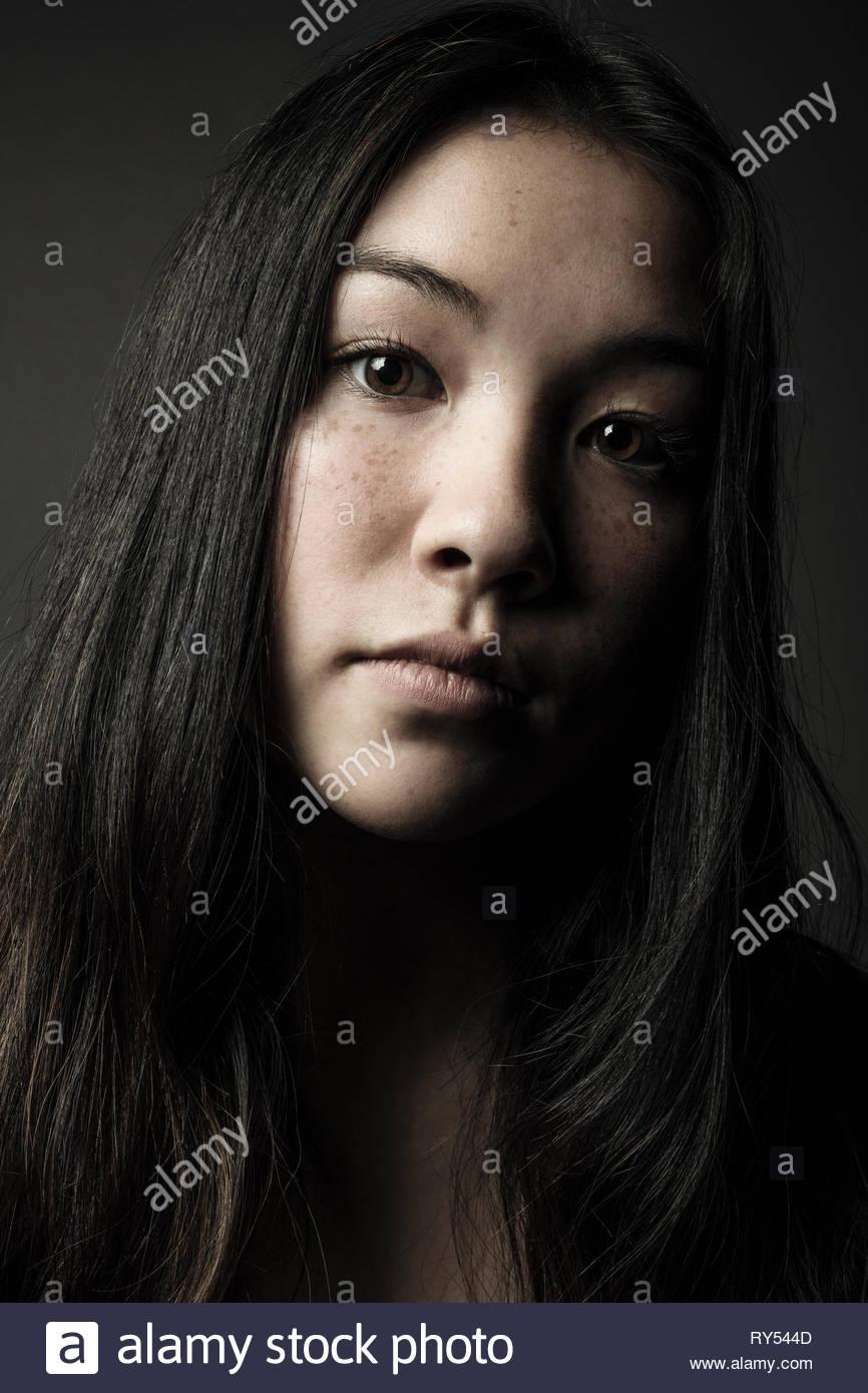 Retrato de cierre seguro hermosa adolescente con largo cabello negro, ojos marrones y pecas Imagen De Stock