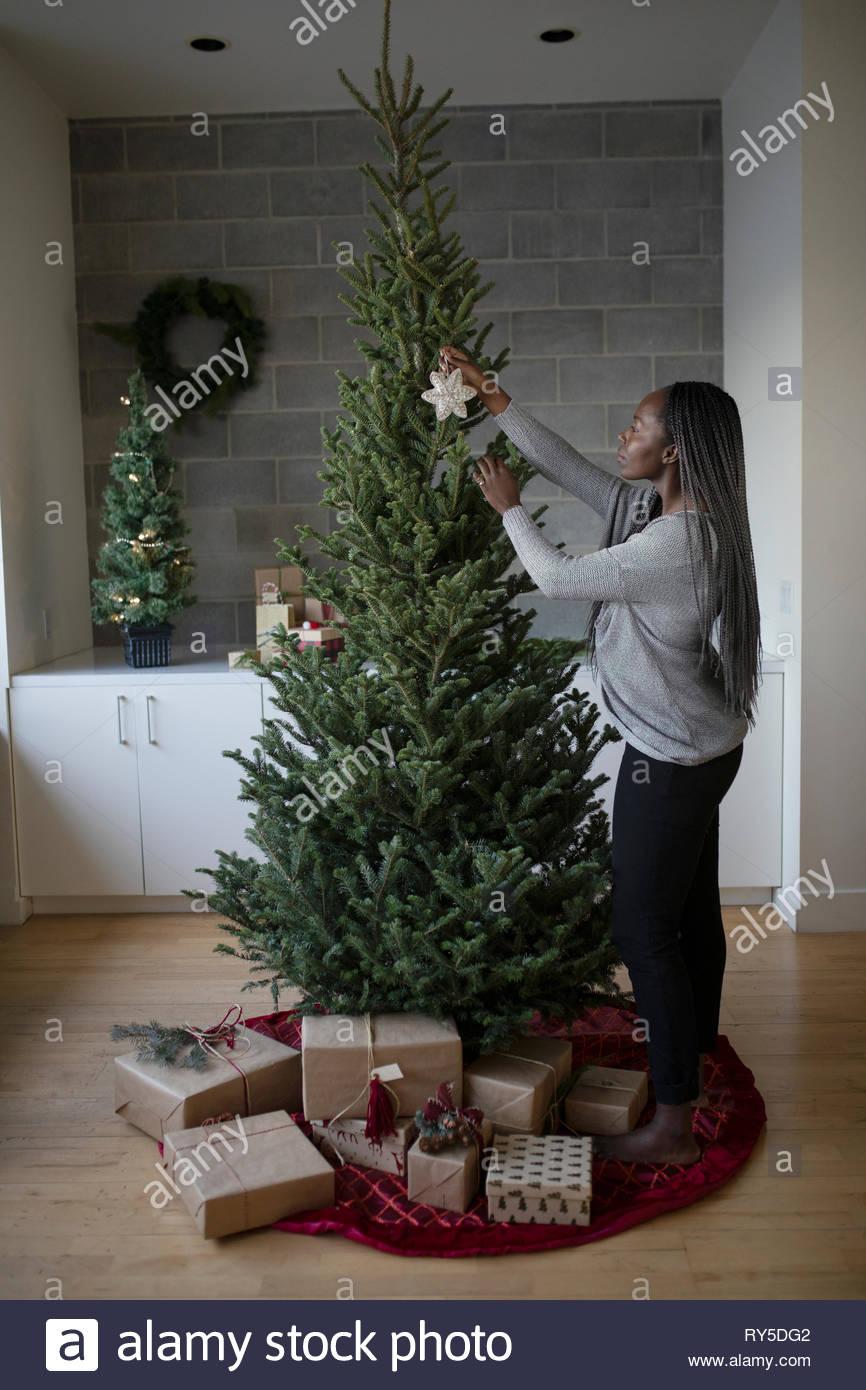 Mujer joven decorar el árbol de navidad Imagen De Stock