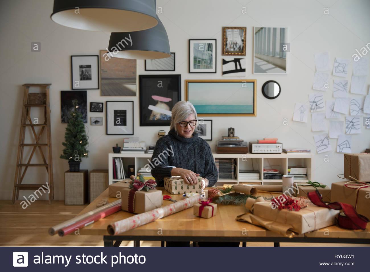 Mujer Senior envolver los regalos de Navidad en studio Imagen De Stock