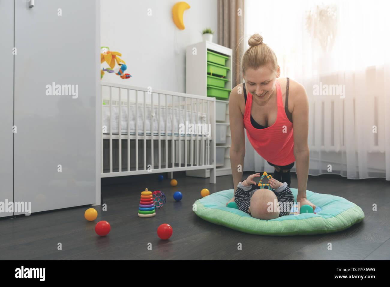 Mujer joven haciendo flexiones en casa mientras juega con su pequeño bebé Foto de stock