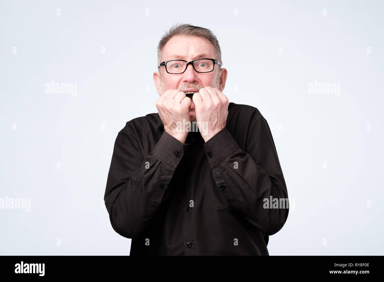 Nervioso hombre senior en vidrios muerde las uñas, parece preocupado antes de médico visitante Imagen De Stock