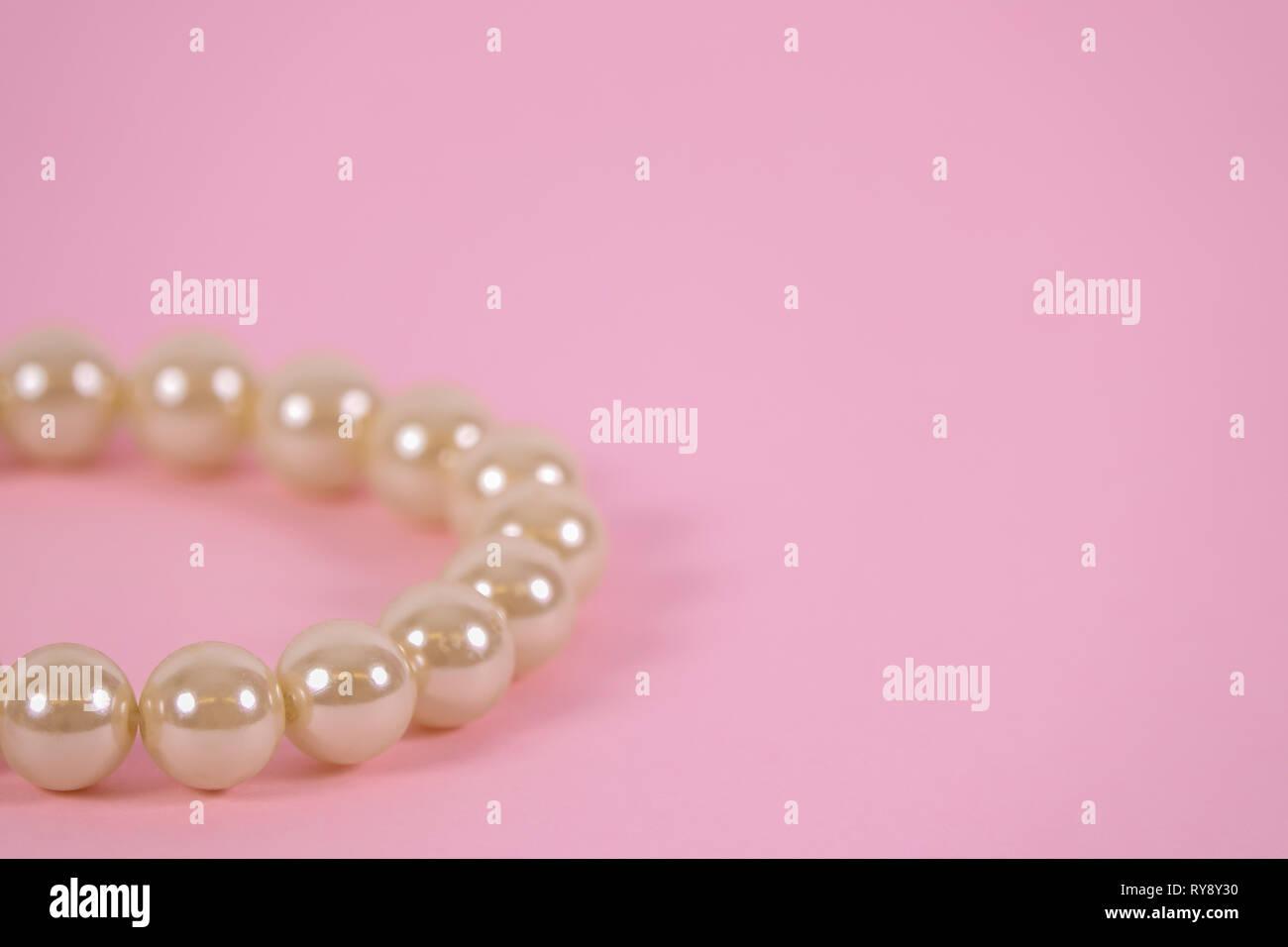 394a3ccc6e51 Una hermosa Pulsera de perlas sobre fondo de color rosa. Copia en blanco el  espacio