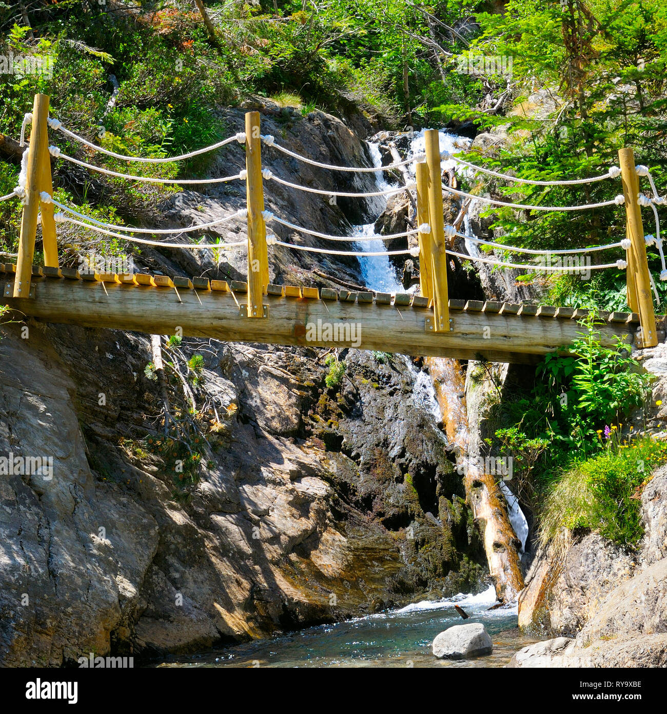 Puente sobre un río de montaña y el banco de grava Foto de stock