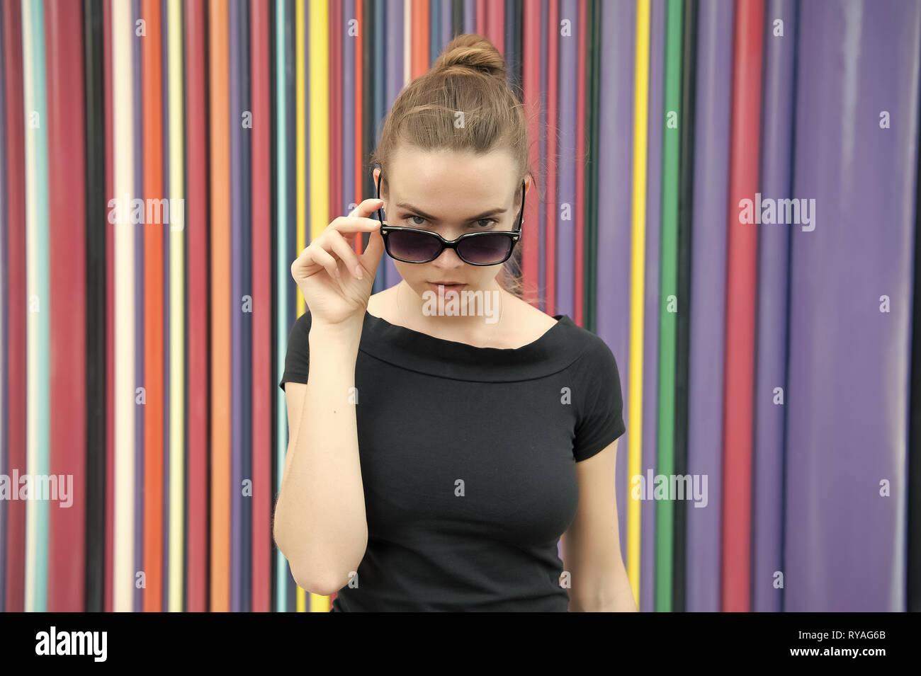 Concepto de estilo urbano de moda. Señora misterioso rostro sacando de anteojos negros en frente de la pared multicolor rayas en París. Mujer elegante apariencia Imagen De Stock