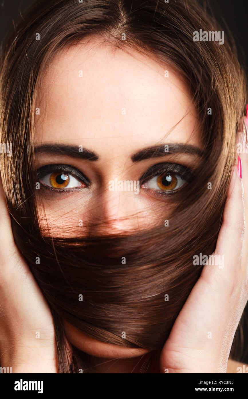 Cerrar mujer cubre el rostro por largos pelos marrones ojos marrones con maquillaje oscuro Foto de stock