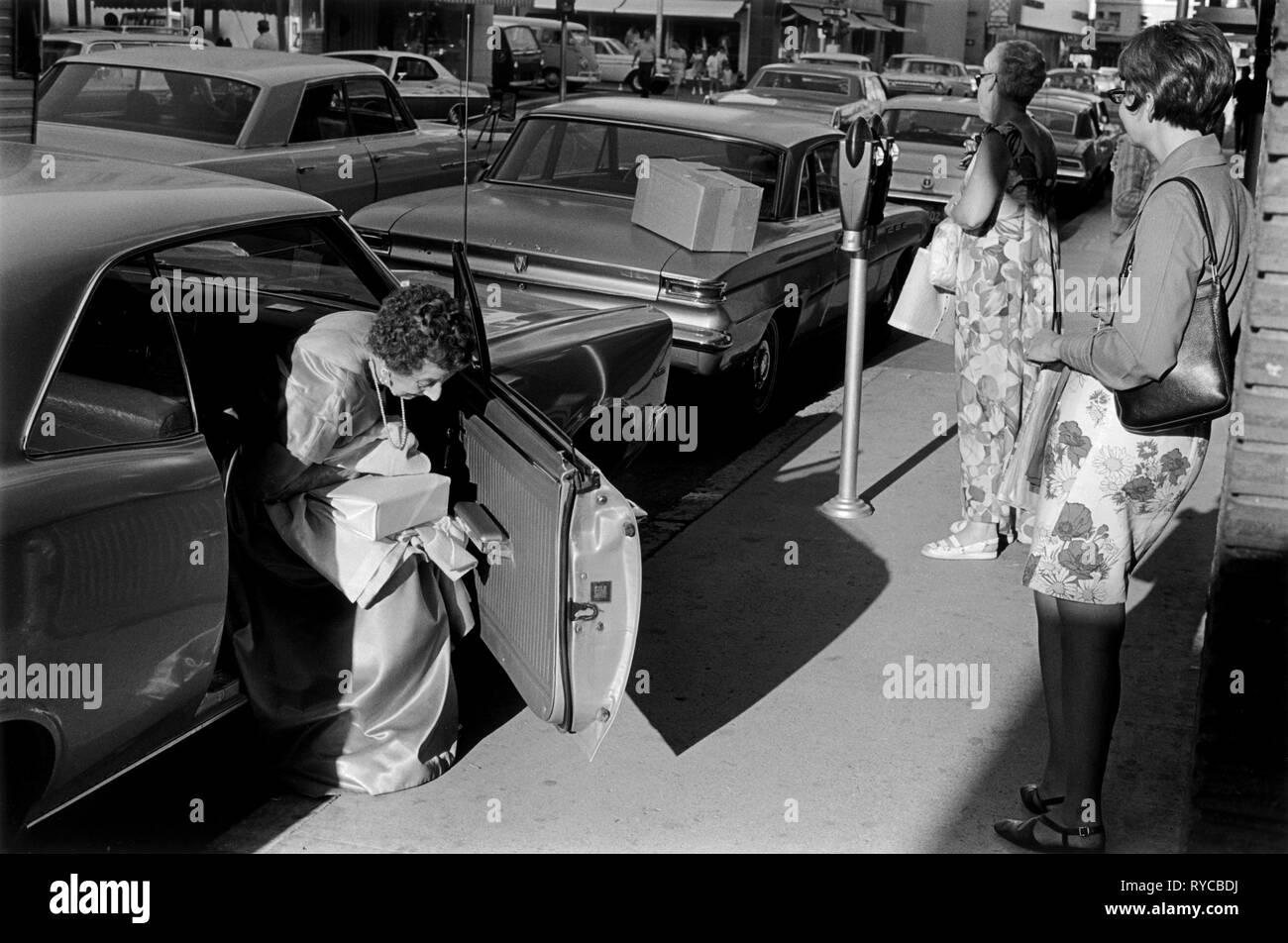Reno Nevada, EE.UU. US 1960, Señoras de poner dinero en el parquímetro antes de ir al Casino vistiendo vestido de fiesta. 60s USA HOMER SYKES Imagen De Stock