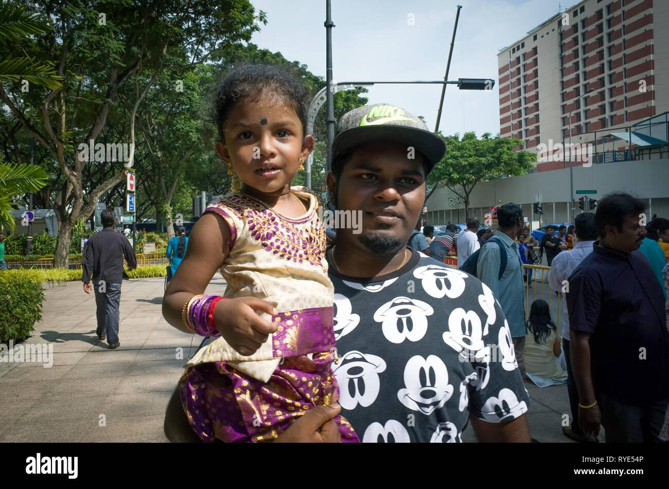 Padre indio mantiene joven hija sonriente en el festival Thaipusam - Singapur Imagen De Stock