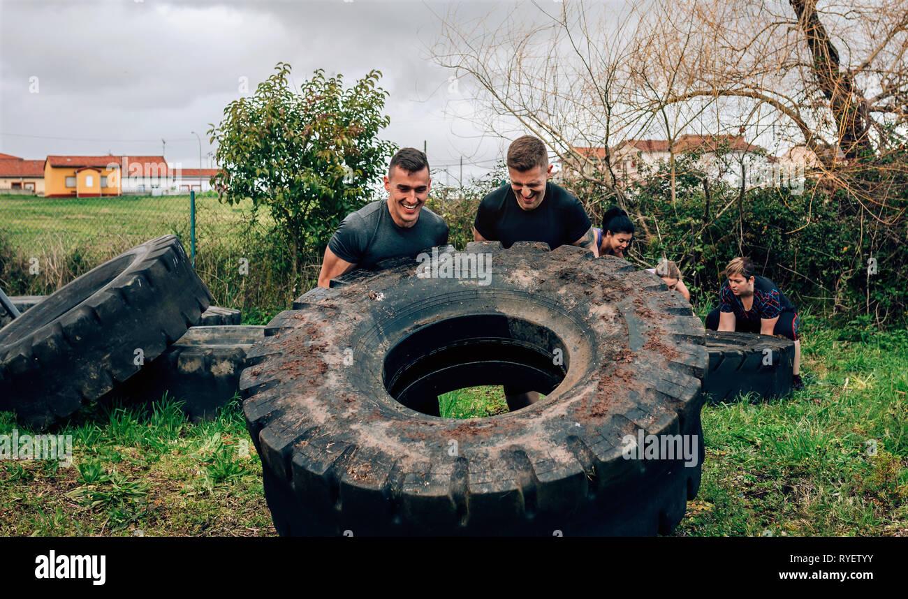 Los participantes en una carrera de obstáculos girando una rueda Foto de stock
