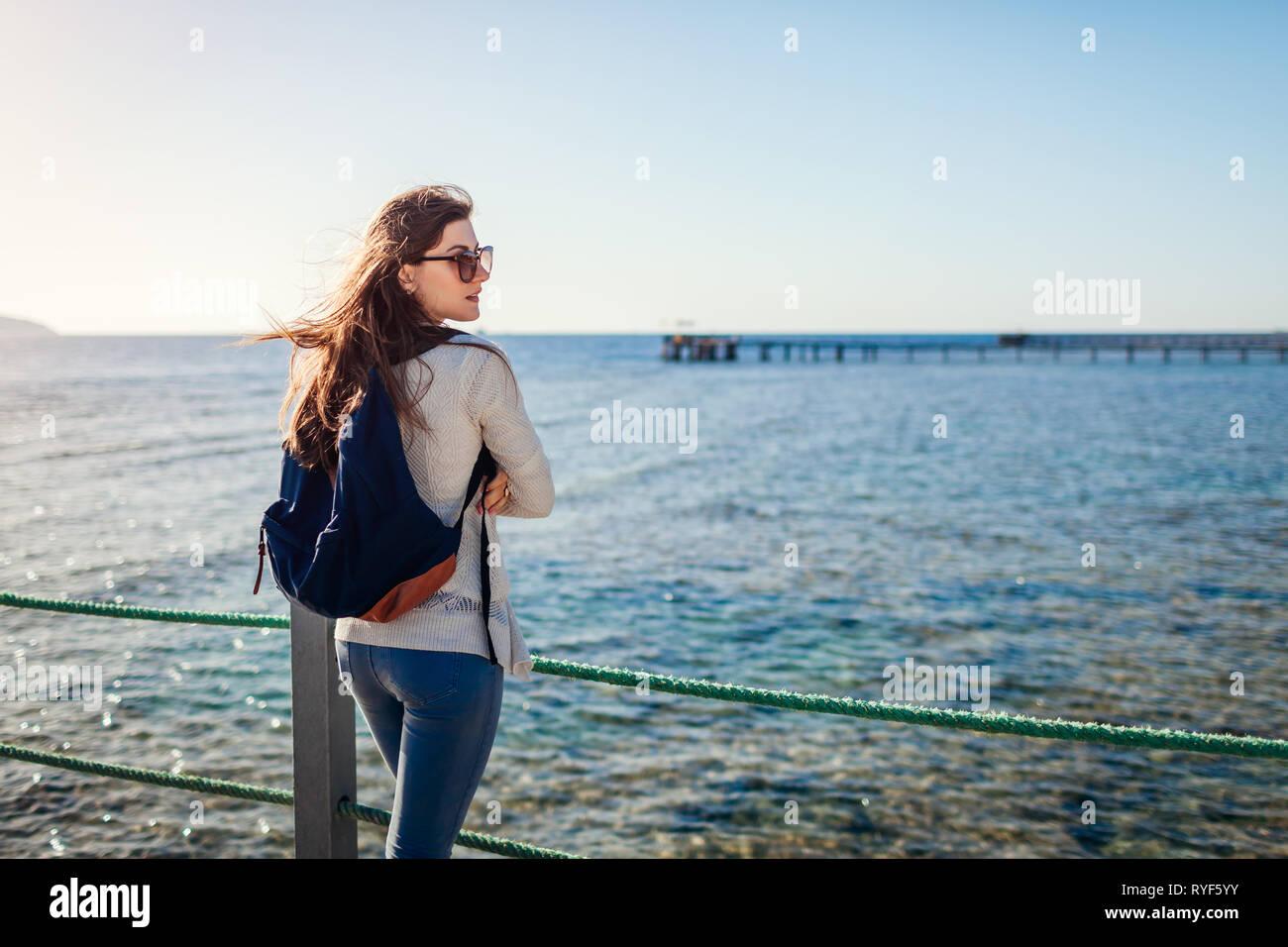 Jóvenes mujeres turistas con mochila admirando el paisaje de mar Rojo caminando en el muelle. Concepto de viaje. Vacaciones de verano Foto de stock