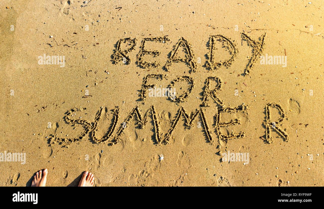 Escritos a mano en la arena preparado para el verano palabras vista superior con los pies, escribiendo en la arena en la playa bajo el cálido sol descalzo - Concepto de preparándose para Imagen De Stock