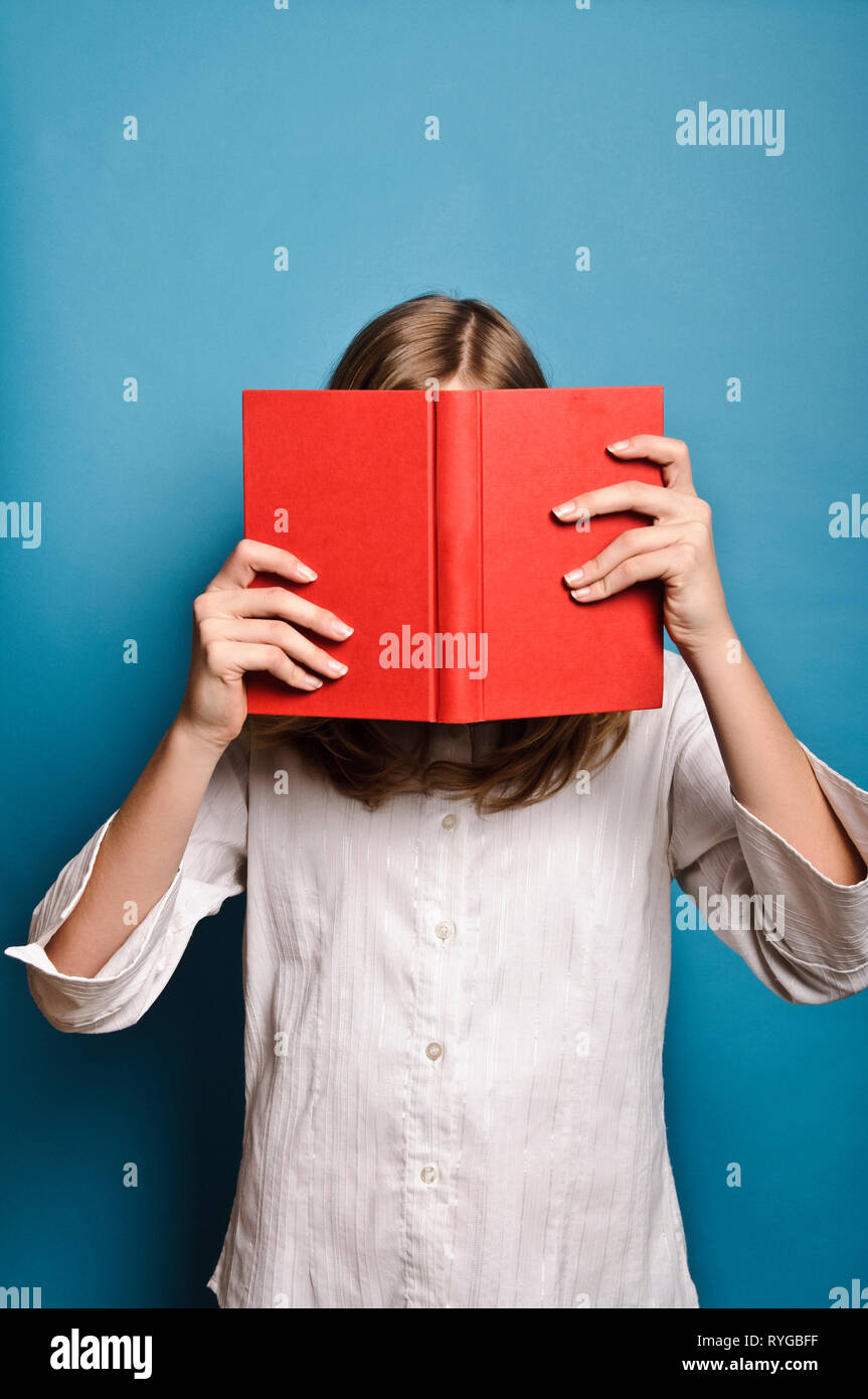 Chica rubia escondiéndose detrás de un libro rojo Imagen De Stock