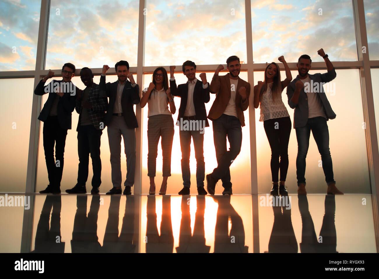 Grupo de jóvenes profesionales de pie en una oficina con una ventana grande Foto de stock