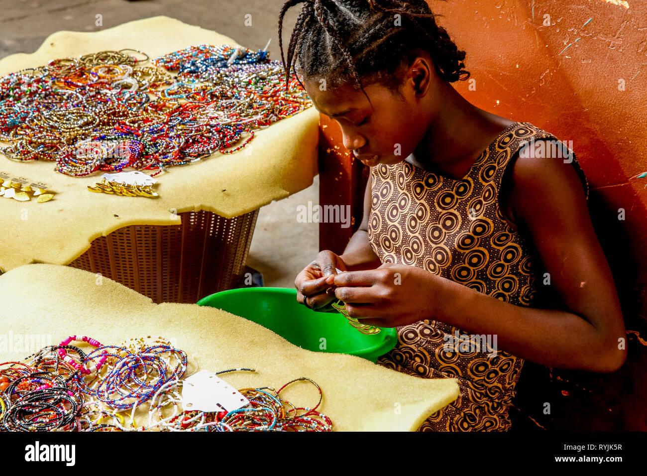 Chica haciendo y vendiendo joyas en Ouagadougou, Burkina Faso. Imagen De Stock