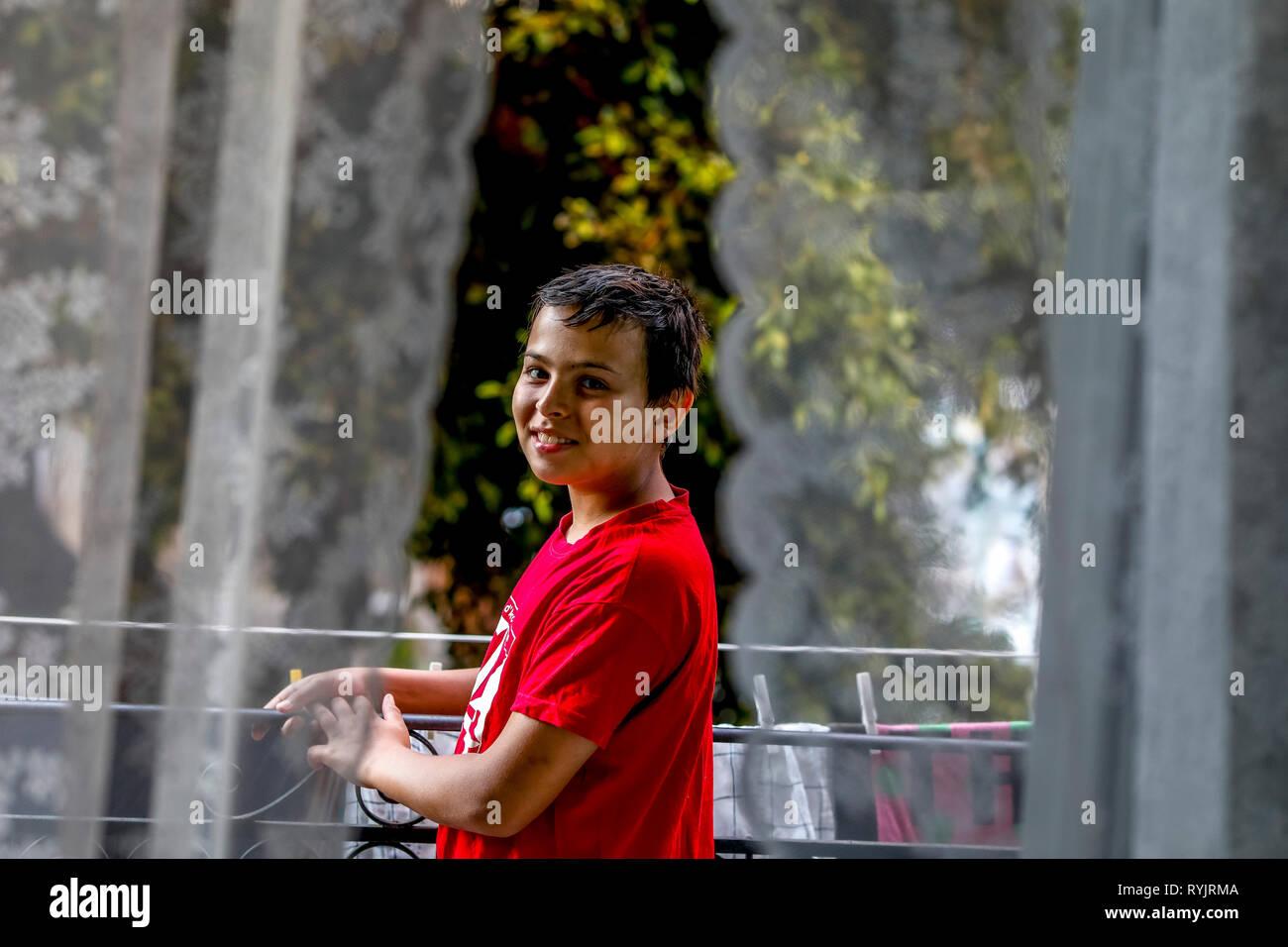 12-año-viejo muchacho de pie en un balcón en Palermo, Sicilia (Italia). Imagen De Stock