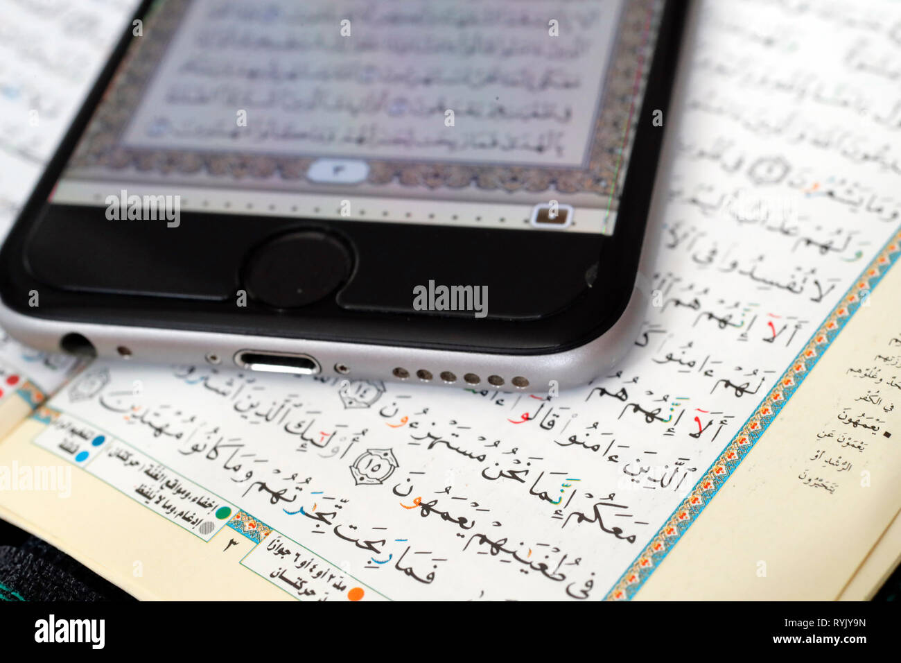 Corán digital en un smartphone y el Sagrado Corán libro. Close-up. Foto de stock