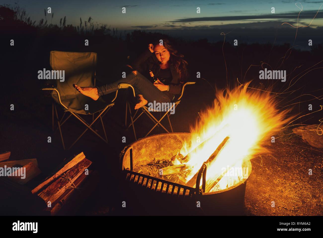 Joven Mujer reflexiva con botella de cerveza está sola cerca de la hoguera y leña en la noche. Barefoot tristeza chica busca en fuego brillante en la oscuridad. Foto de stock