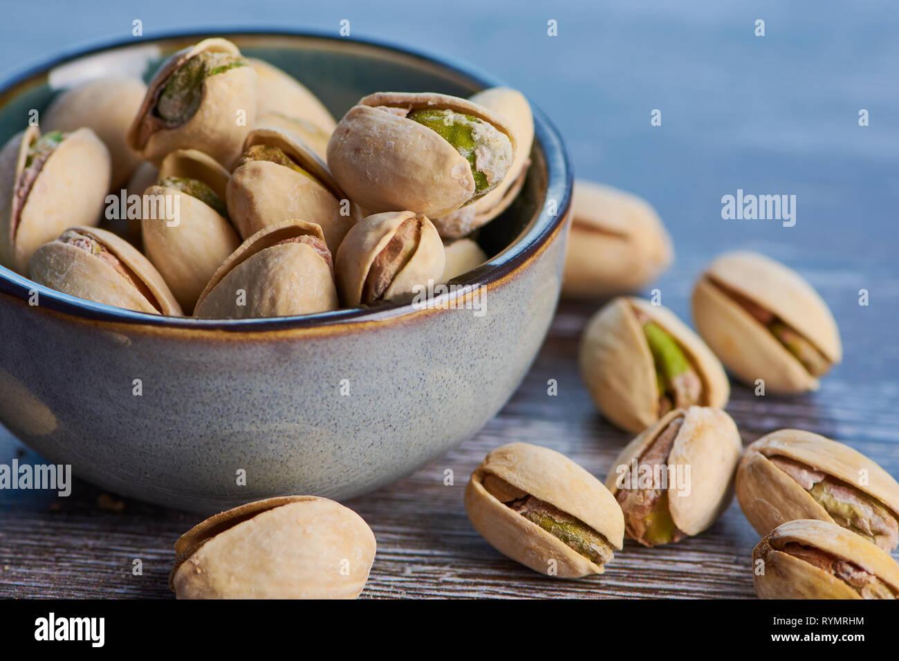 Cerca de pistachos imágenes en color tostado y salado en un cuenco de cerámica sobre una superficie de madera Foto de stock