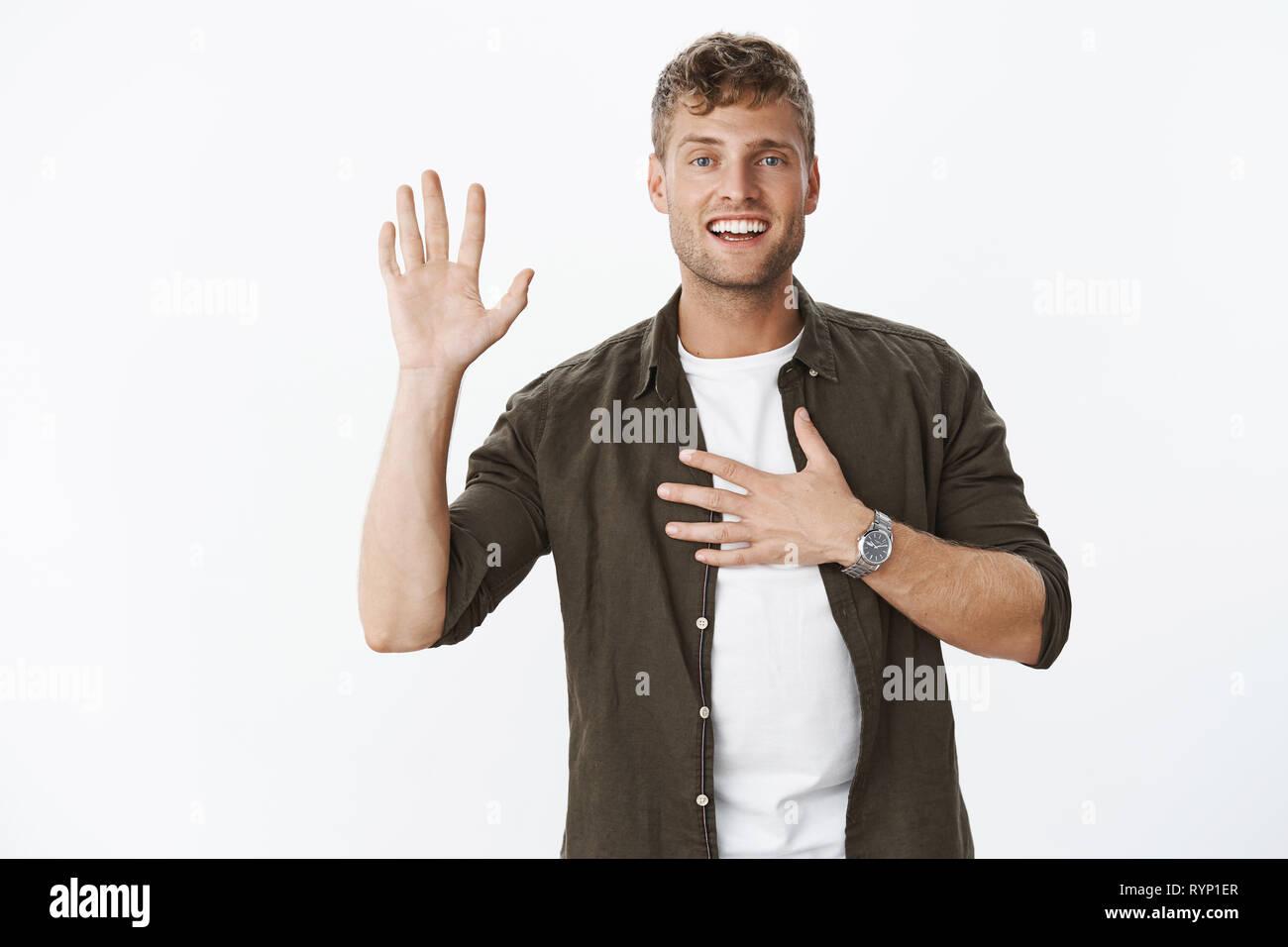 Te juro. Retrato de aspecto agradable, encantador y carismático masculino maduro macho con pelos justo palm y sujetando con la mano en el corazón, como Imagen De Stock