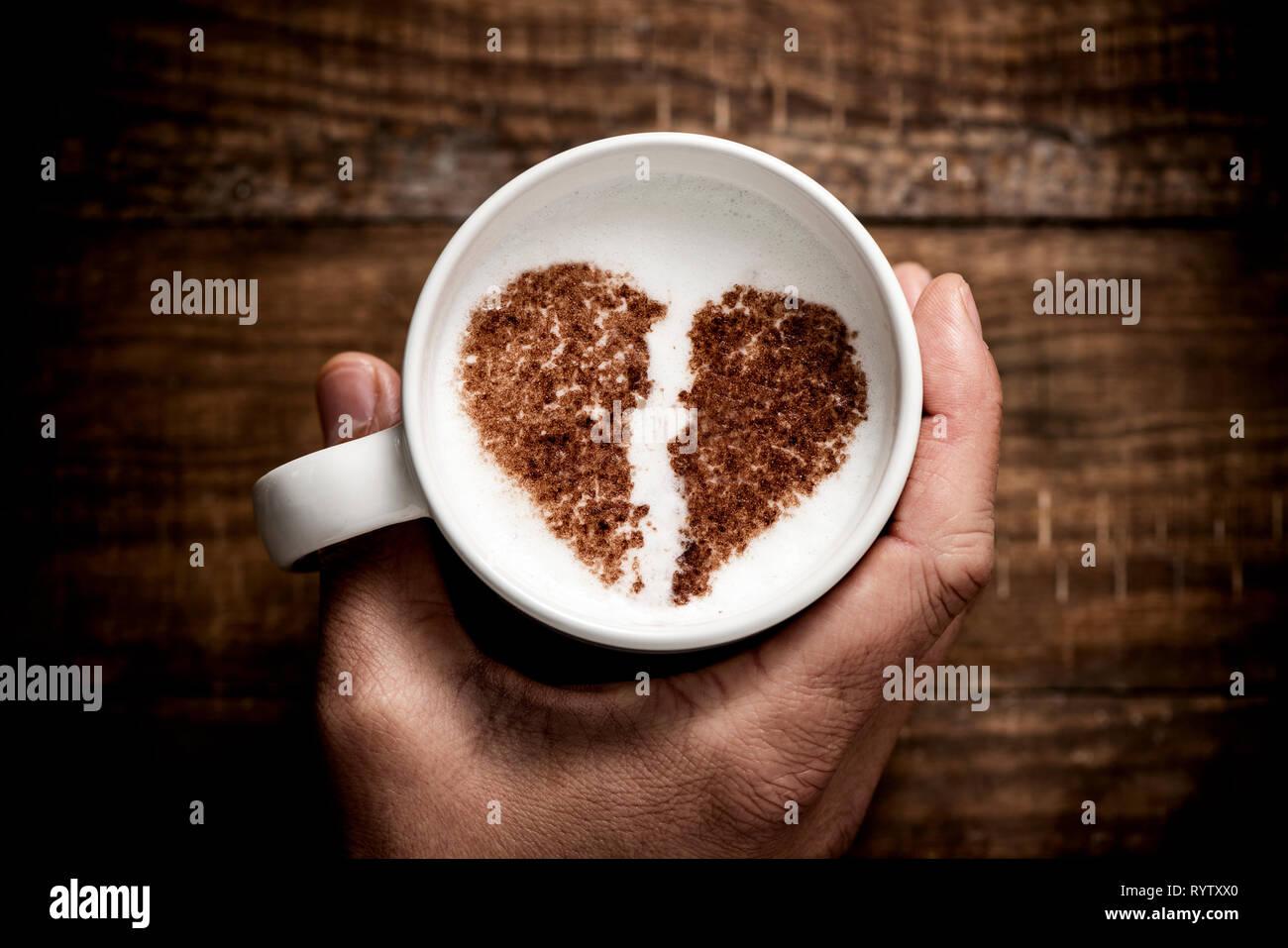 Un alto ángulo de visualización de un hombre caucásico sosteniendo una taza de cerámica blanca de capuchino, con el corazón roto dibujado con cacao en polvo sobre la espuma de leche, en un rusti Imagen De Stock