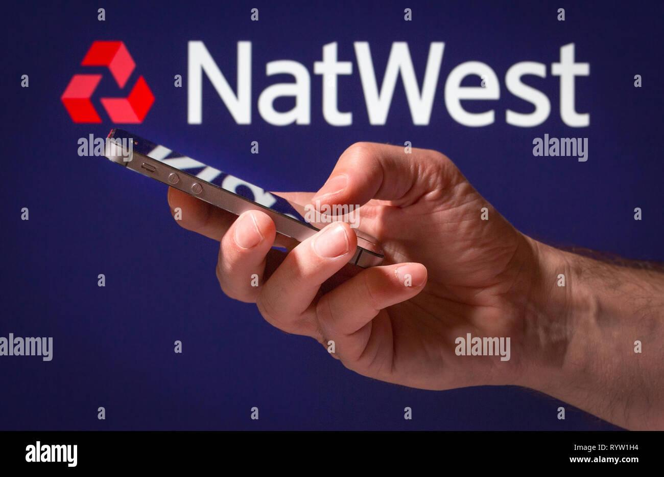 Un hombre usando Natwest banca en línea en su teléfono móvil Imagen De Stock