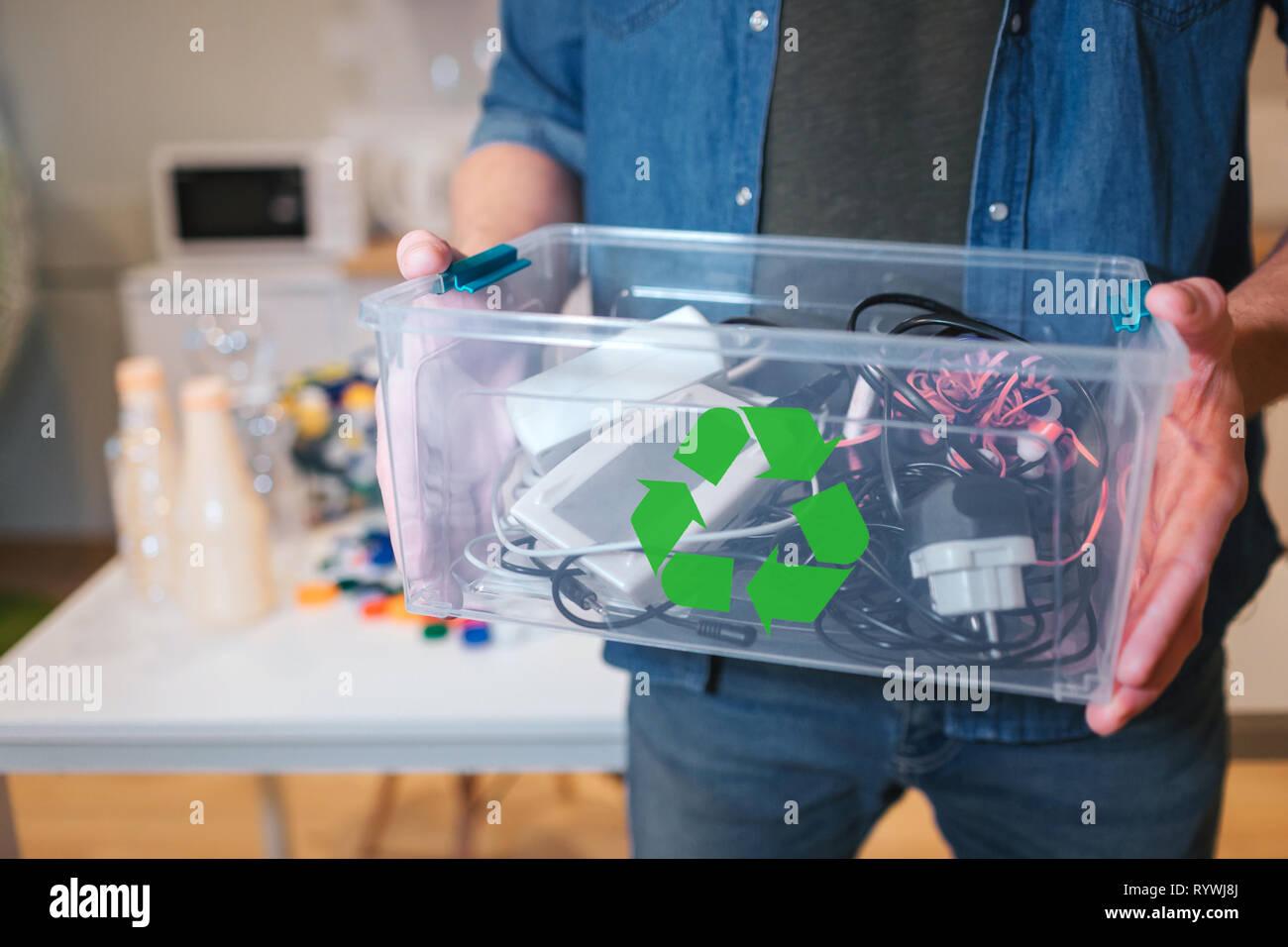 Concepto de reciclaje. En el reciclaje de residuos electrónicos contaner cerca. Hombre responsable es proteger el medio ambiente mientras que clasificar los residuos en casa Imagen De Stock