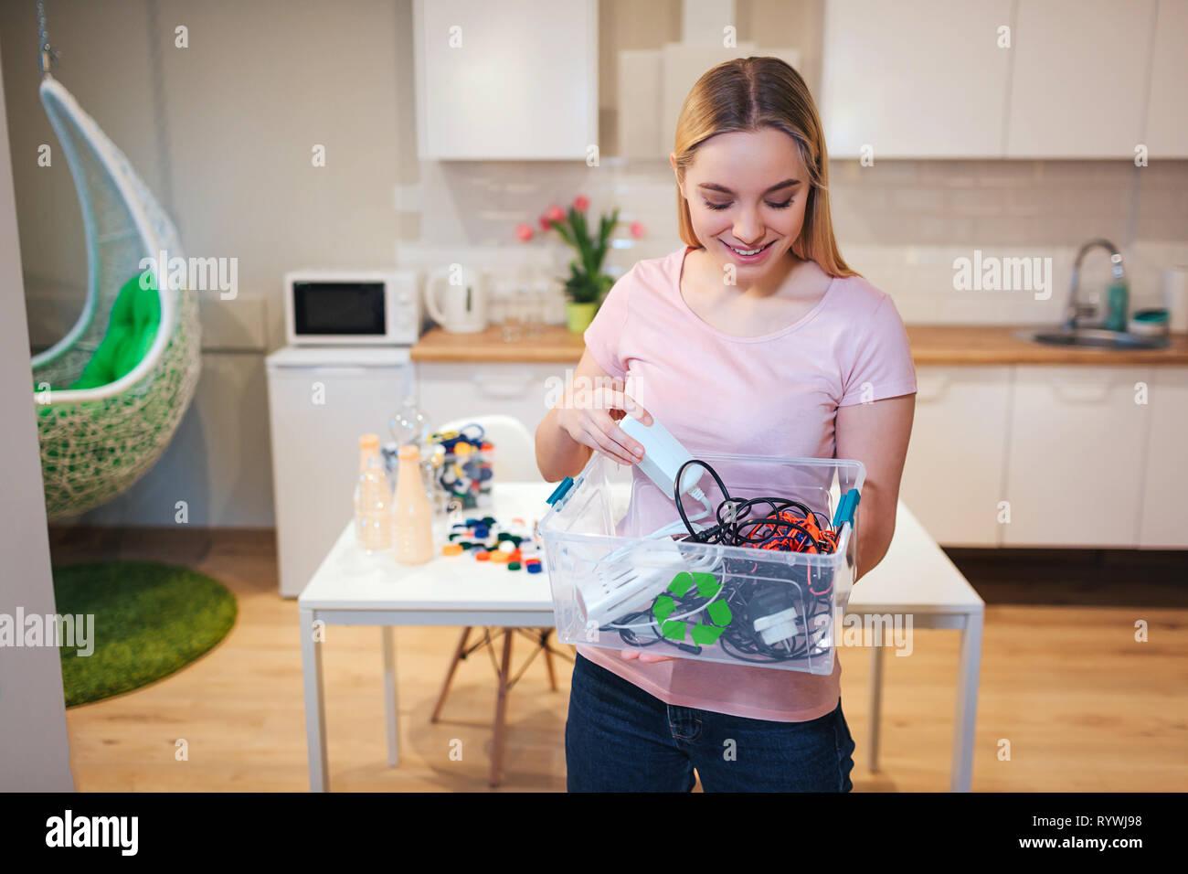 Reciclaje. Joven Mujer sonriente Celebración de desechos electrónicos en el contenedor con icono verde reciclar sobre fondo de cocina Imagen De Stock